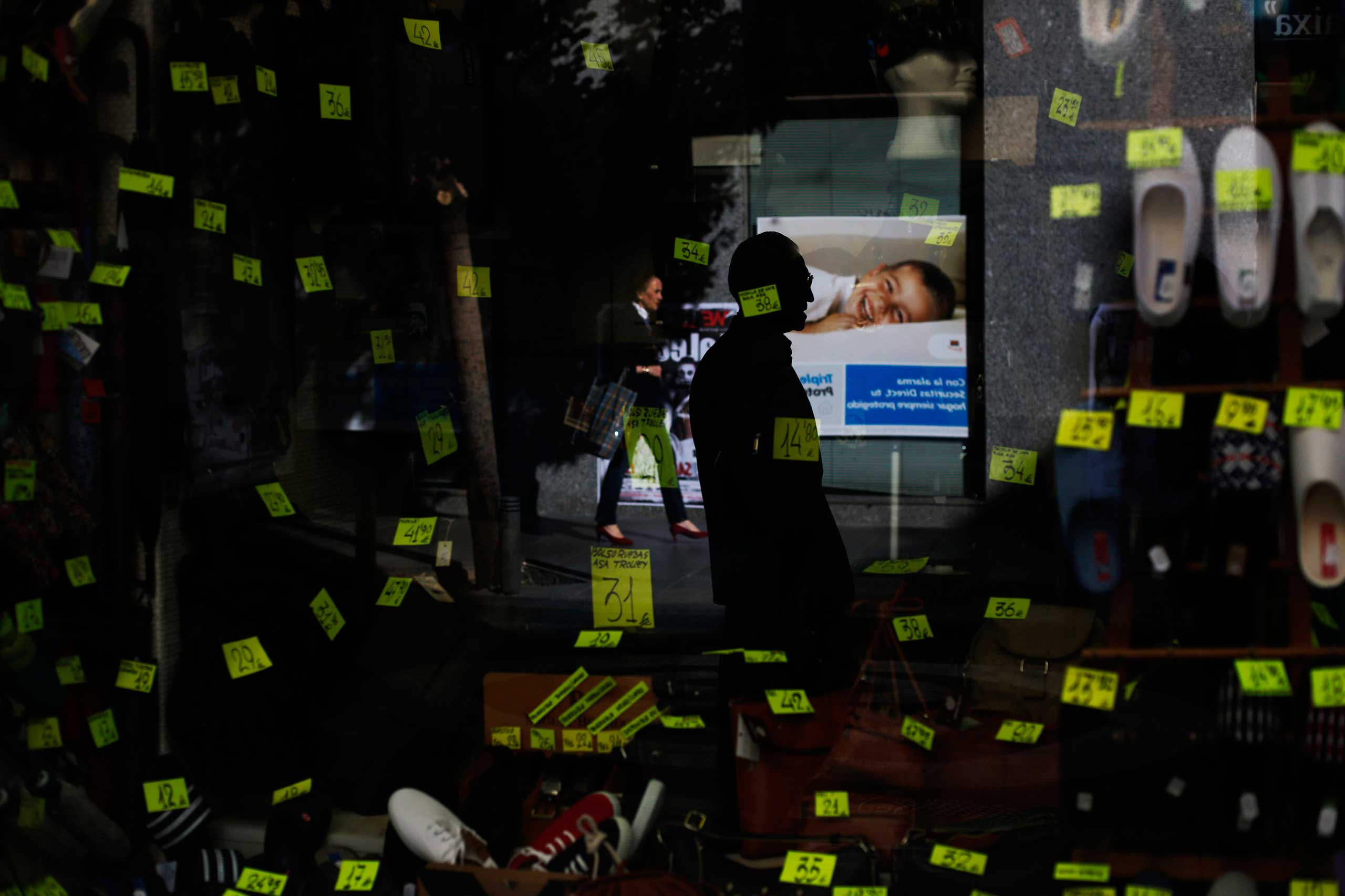 Oct. 30, 2014. People are reflected in the window of a shoe and handbag store in central Madrid. Spain's economy expanded for the fifth quarter running between July and September, but a slowing rate of growth along with falling consumer prices suggested the recovery may be losing momentum.