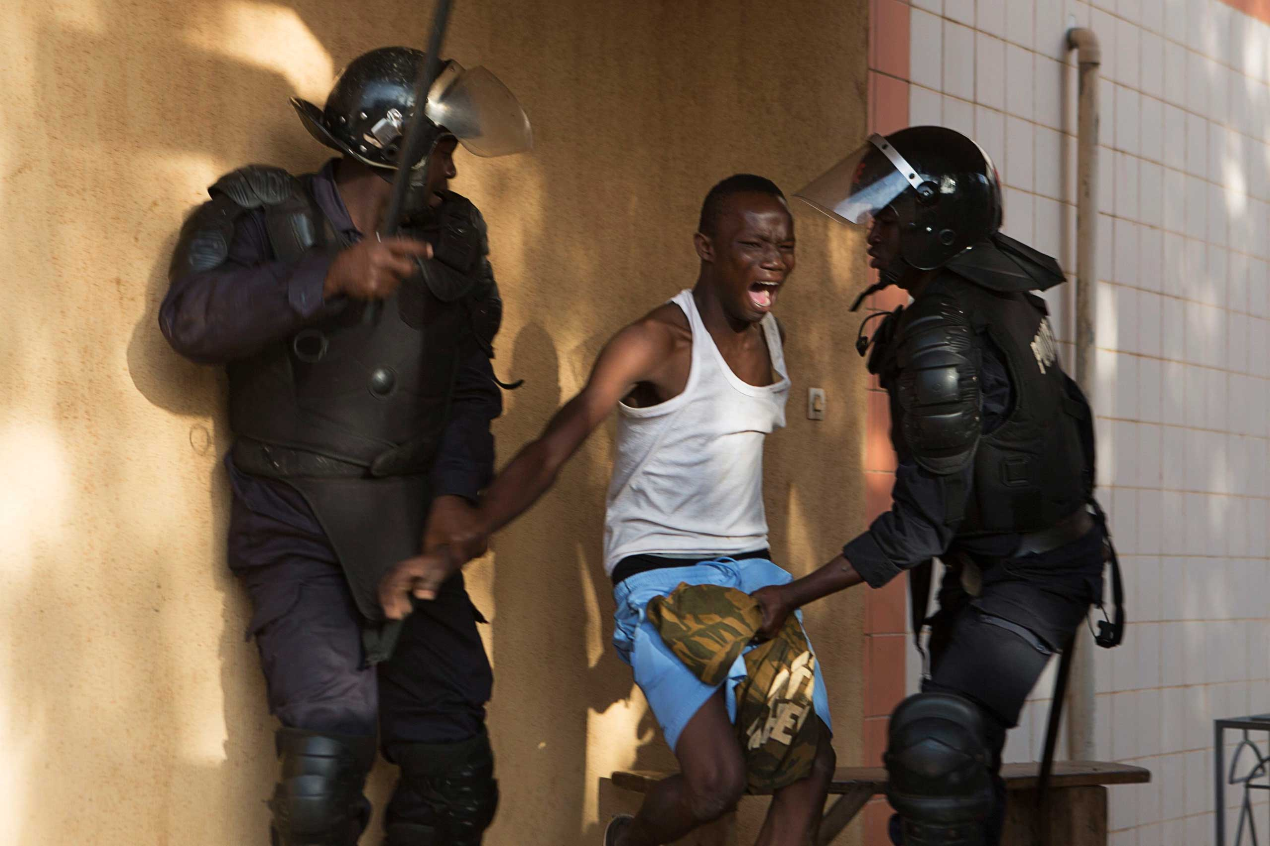 Oct. 30, 2014. Riot police arrest an anti-government protester in Ouagadougou, capital of Burkina Faso.  Thousands of protesters marched on Burkina Faso's presidential palace after burning the parliament building and ransacking state television offices on Thursday, forcing President Blaise Compaore to scrap a plan to extend his 27-year rule.
