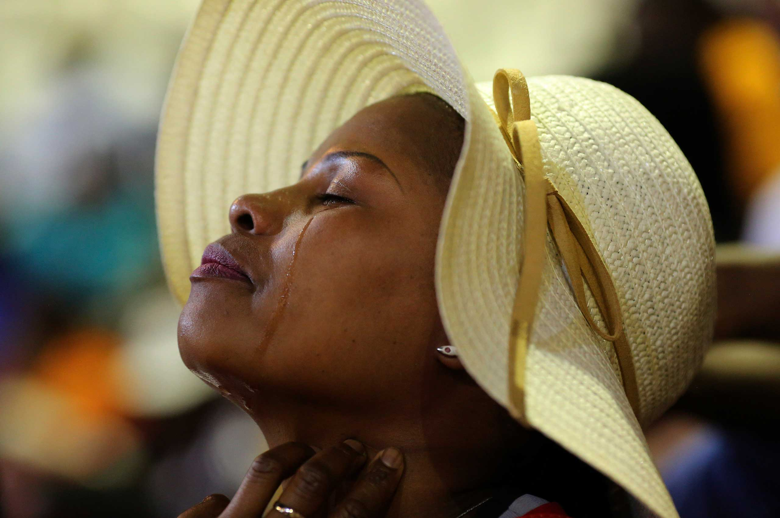 Oct. 27, 2014. A woman reacts during a joint memorial service Johannesburg for South African athletes, national soccer captain Senzo Meyiwa, female professional boxer Phindile Mwelase and Olympic silver medallist Mbulaeni Mulaudzi.