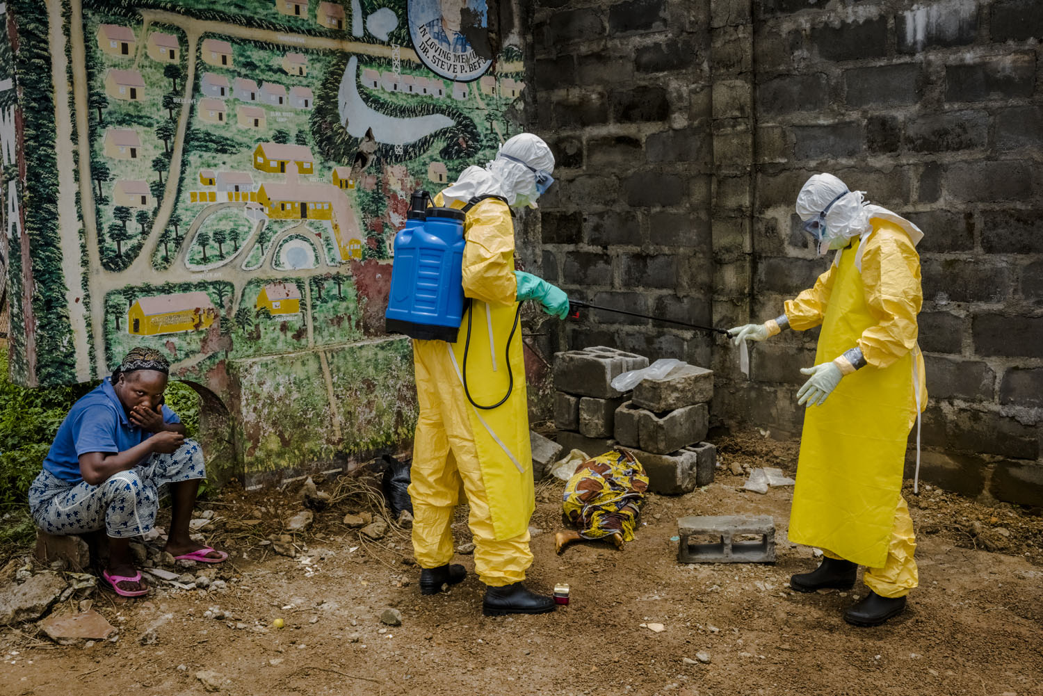 Medical staff spray down a small plastic bag containing the blood sample of Hawa Konneh, 9, a suspected Ebola victim, as she lays on the dirt wrapped in a shawl in front of the Doctors Without Borders (MSF) Ebola treatment center, as her mother, Masogbe, sits near to her prior to Hawa's passing away on Sept. 4, 2014 in Monrovia, Liberia.