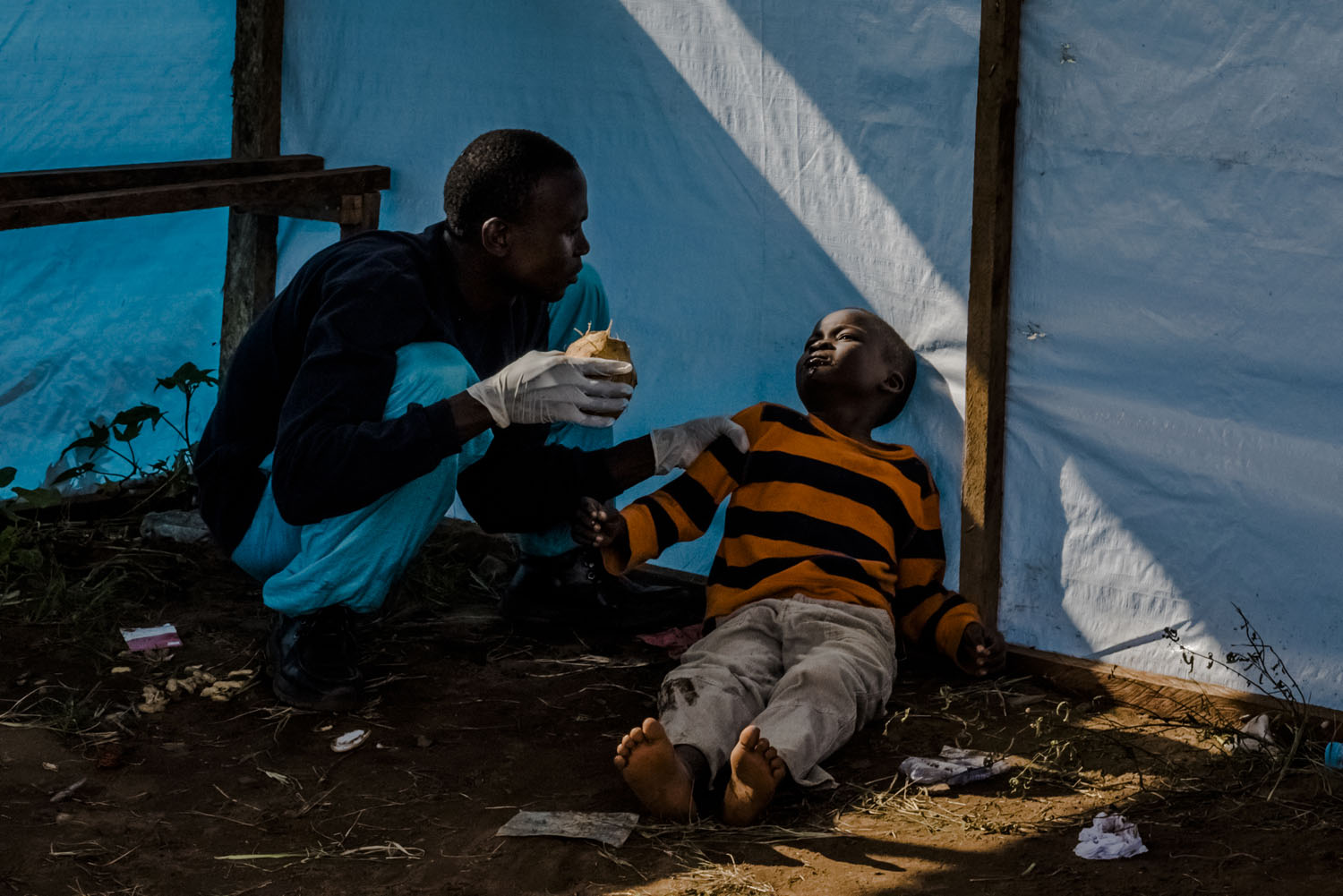 James Dorbor, 8, suspected to have Ebola, lays on the ground as his father Edward tried to get the boy to drink coconut water. They waited for James to be admitted into the JFK Ebola treatment center on Sept. 5, 2014 in Monrovia, Liberia.