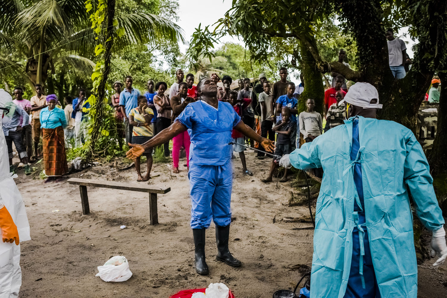 A member of a Liberian Red Cross burial team is disinfected, with chlorine sprayed on by a colleague, after having  removed the body of a man, a suspected Ebola victim, on Sept. 6, 2014 in Monrovia, Liberia.