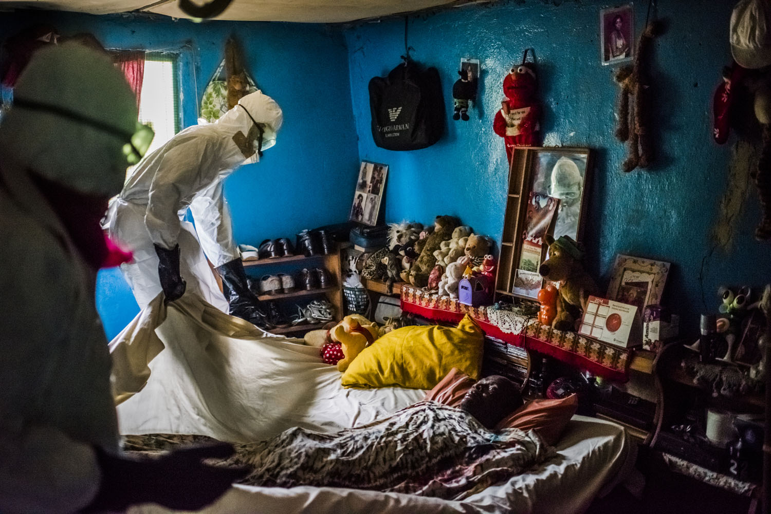 Members of a burial team from the Liberian Red Cross remove the body of a man, a suspected Ebola victim, from a home in Matadi on Sept. 17, 2014 in Monrovia, Liberia.