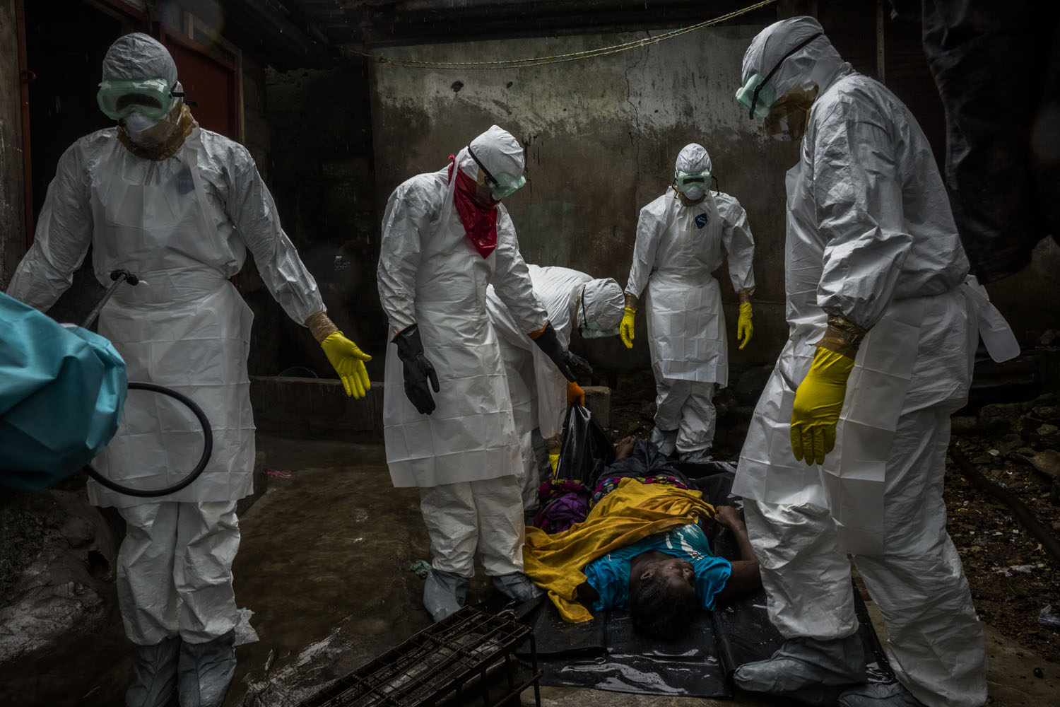 Members of a Liberian Red Cross burial team, under contract from the Liberian Ministry of Health, remove the body of a suspected Ebola victim Lorpu David, 30 on Sept. 18, 2014 in the Gurley street community in central Monrovia, Liberia.