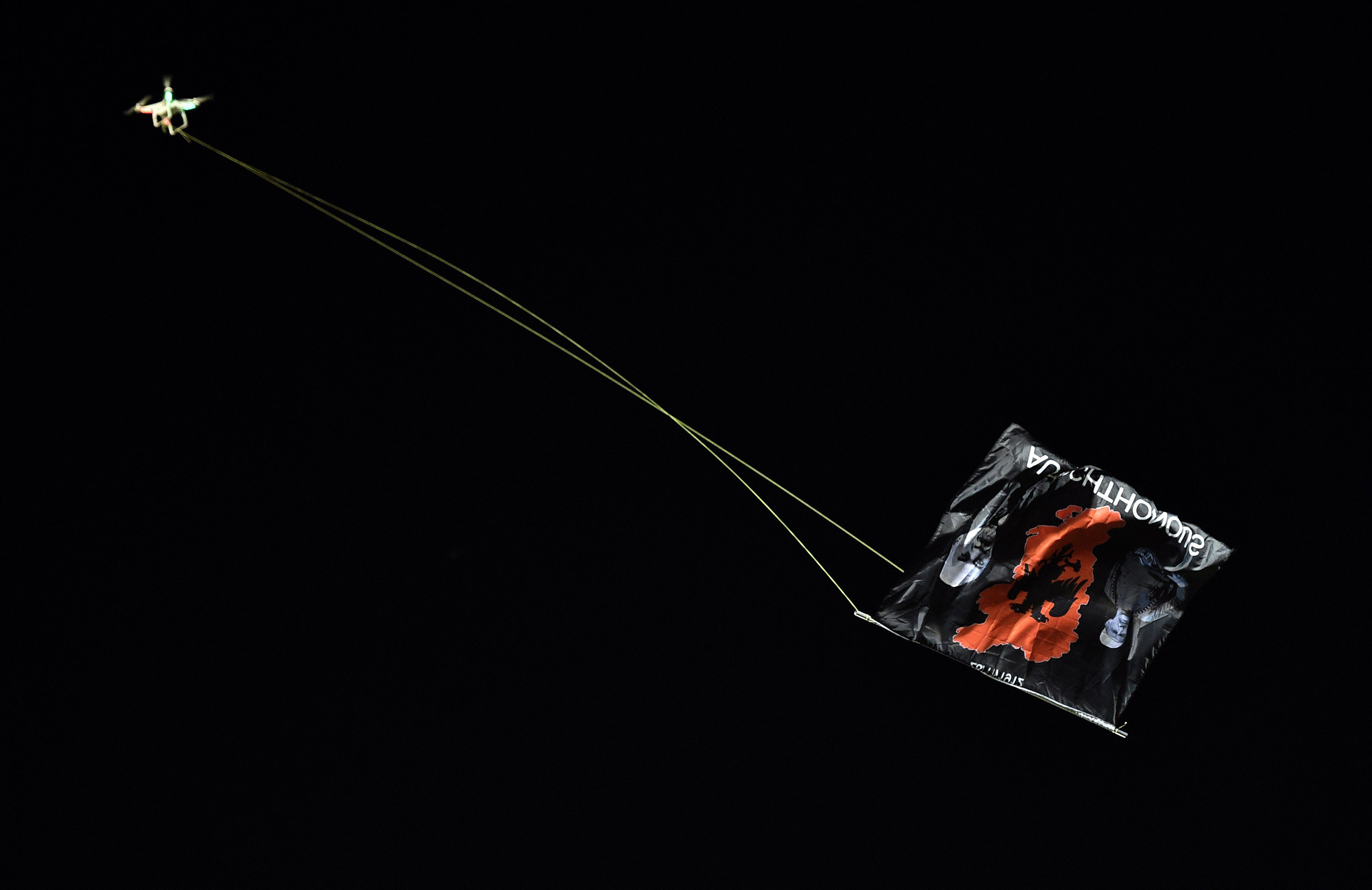 A flag with Albanian national symbols attached to a remotely operated drone flies in the stadium  during the EURO 2016 group I football match between Serbia and Albania in Belgrade, Serbia on Oct. 14, 2014.