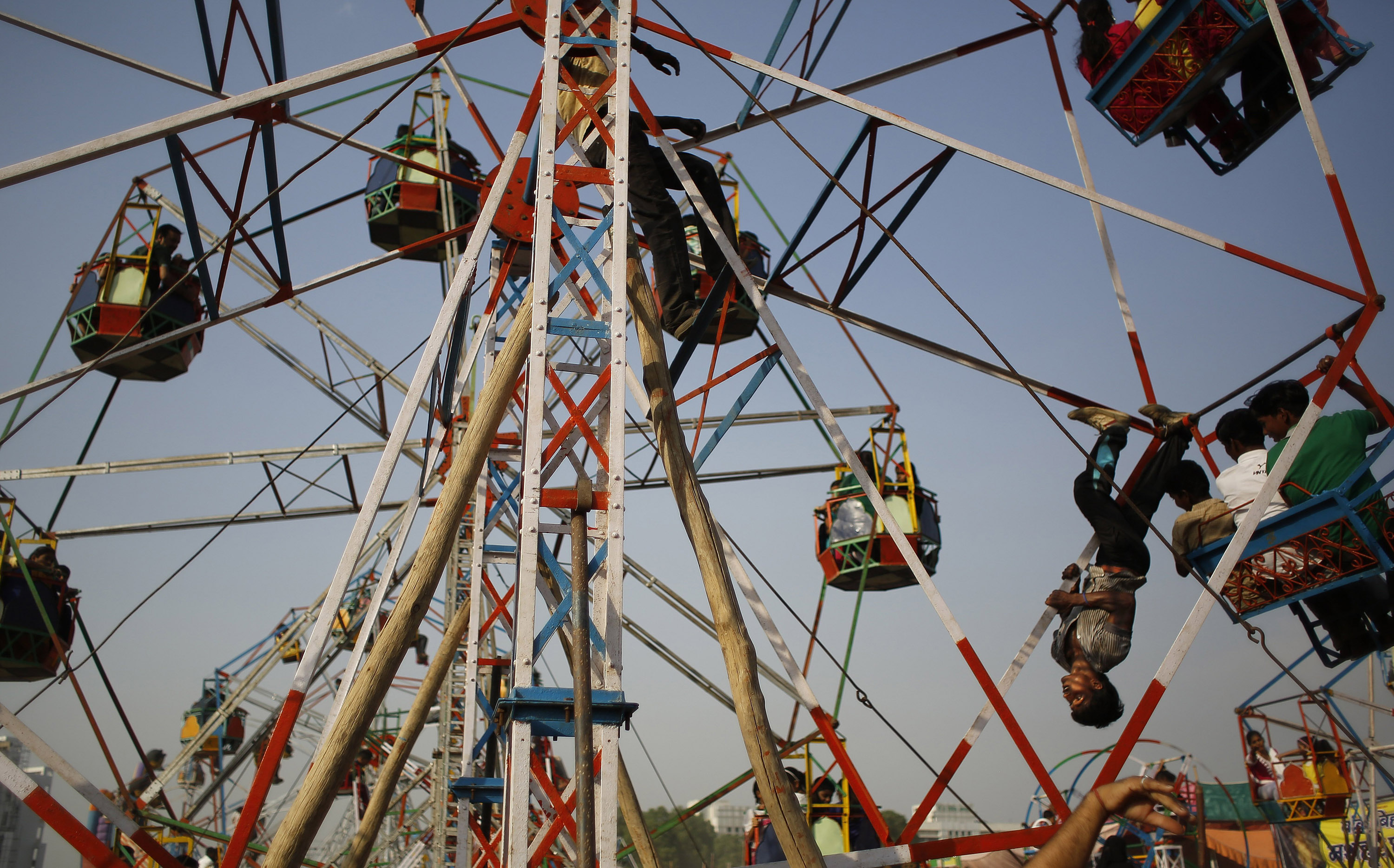An Indian worker rides upside down to push a giant wheel at a fair ground during Dussehra celebrations on the outskirts of New Delhi, Oct. 3, 2014.