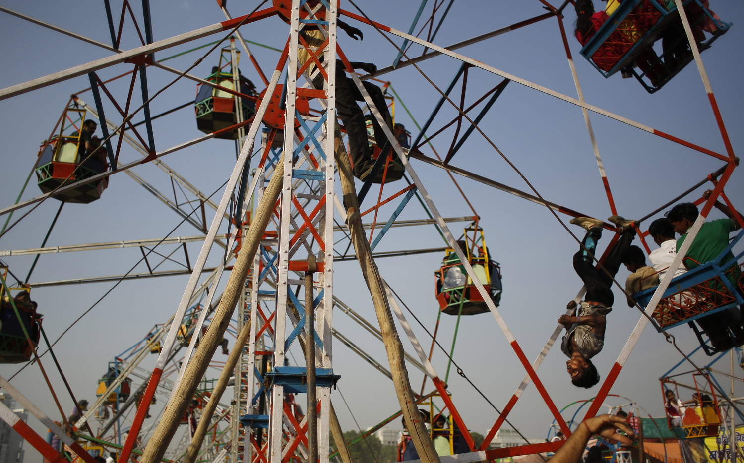 An Indian worker rides upside down to push a giant wheel at a fair ground before the burning of effigies of demon king Ravana during Dussehra celebrations on the outskirts of New Delhi, India, on Oct. 3, 2014.