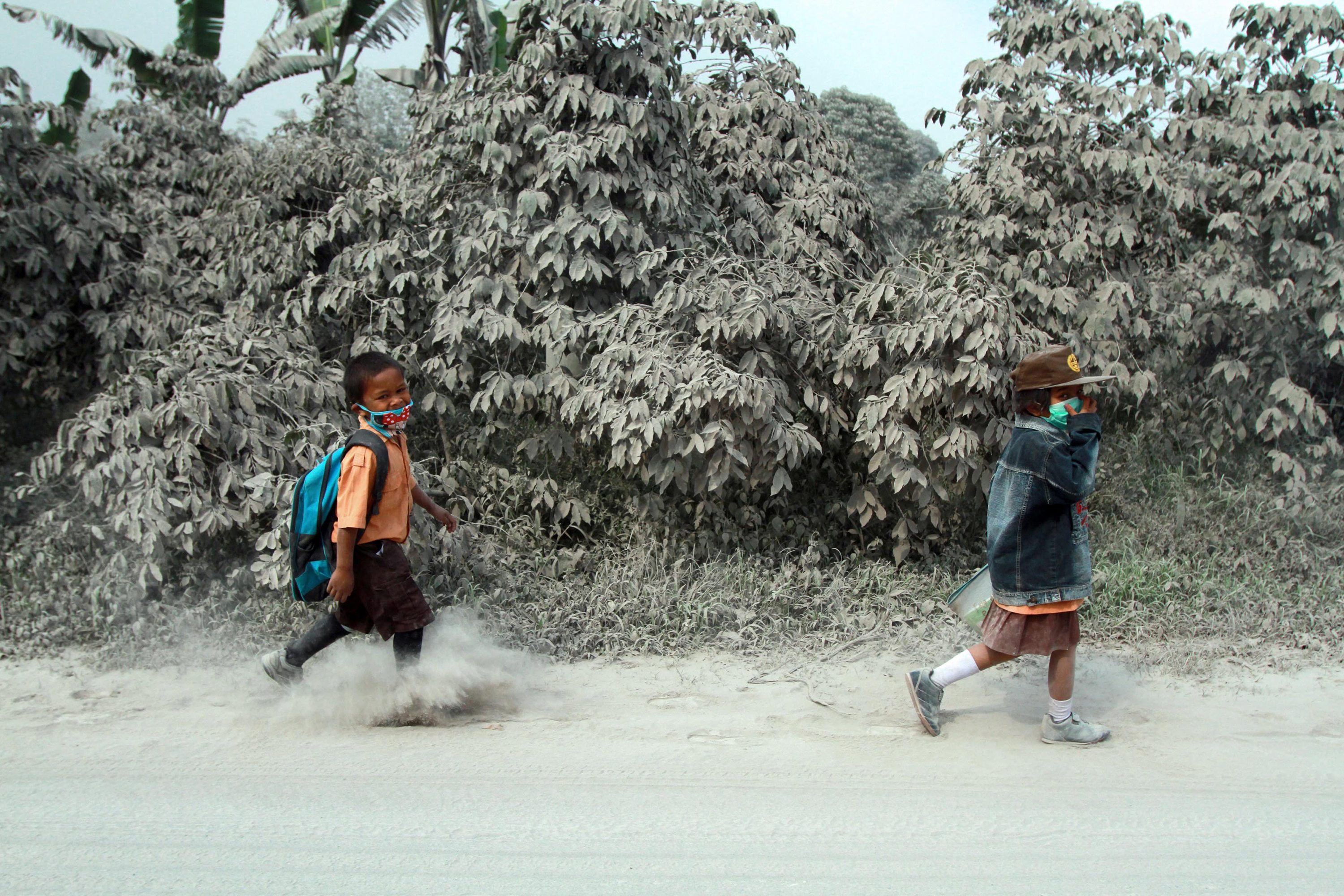 Indonesian students walk on a street covered in Mount Sinabung volcanic ash in Sukandebi village, North Sumatra, Indonesia, on Oct. 10, 2014.