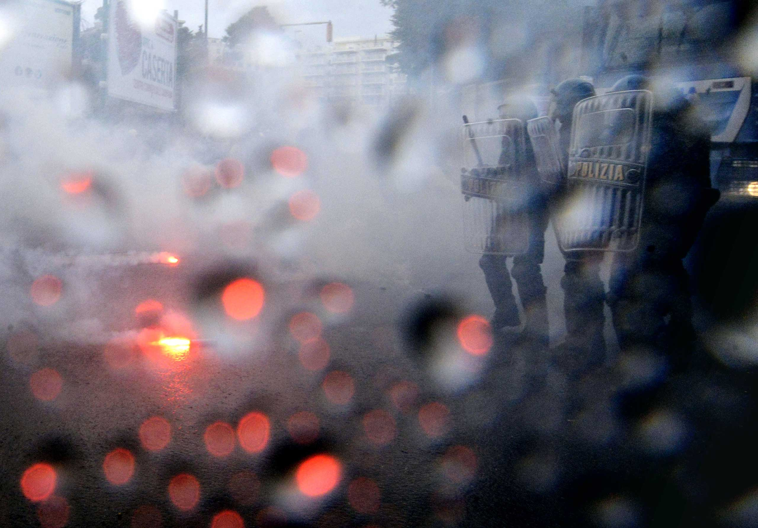 Oct. 2, 2014. Demonstrators, targeted by water cannons, throw flares at police as the ECB governing council meets in Naples, Italy.