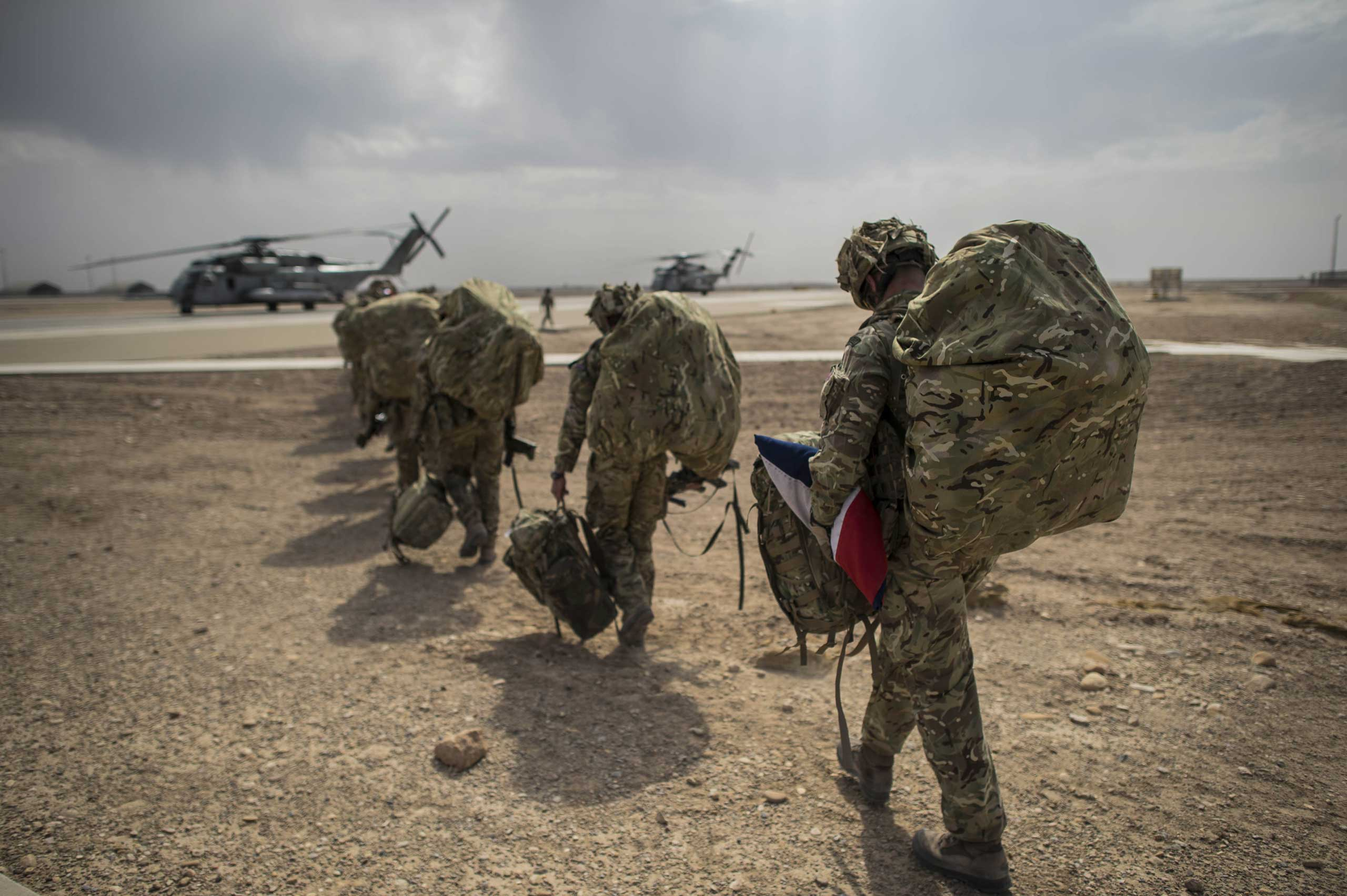 Oct. 27, 2014. Wing Commander Matt Radnall, Officer Commanding 7 Force Protection Wing, carries a carefully folded U.K. flag under his arm as he walks out towards helicopter to go back home to the U.K. He is one of the last British boots to leave Camp Bastion in Helmand Province, Afghanistan.