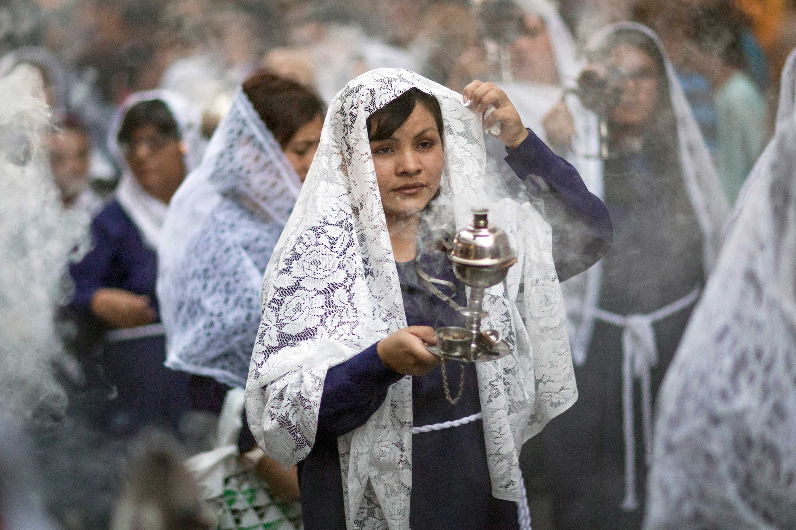 Oct. 26, 2014. Women carry censers as they participate in a procession honoring The Lord of Miracles the patron saint of most Catholic Peruvians, in Madrid.
