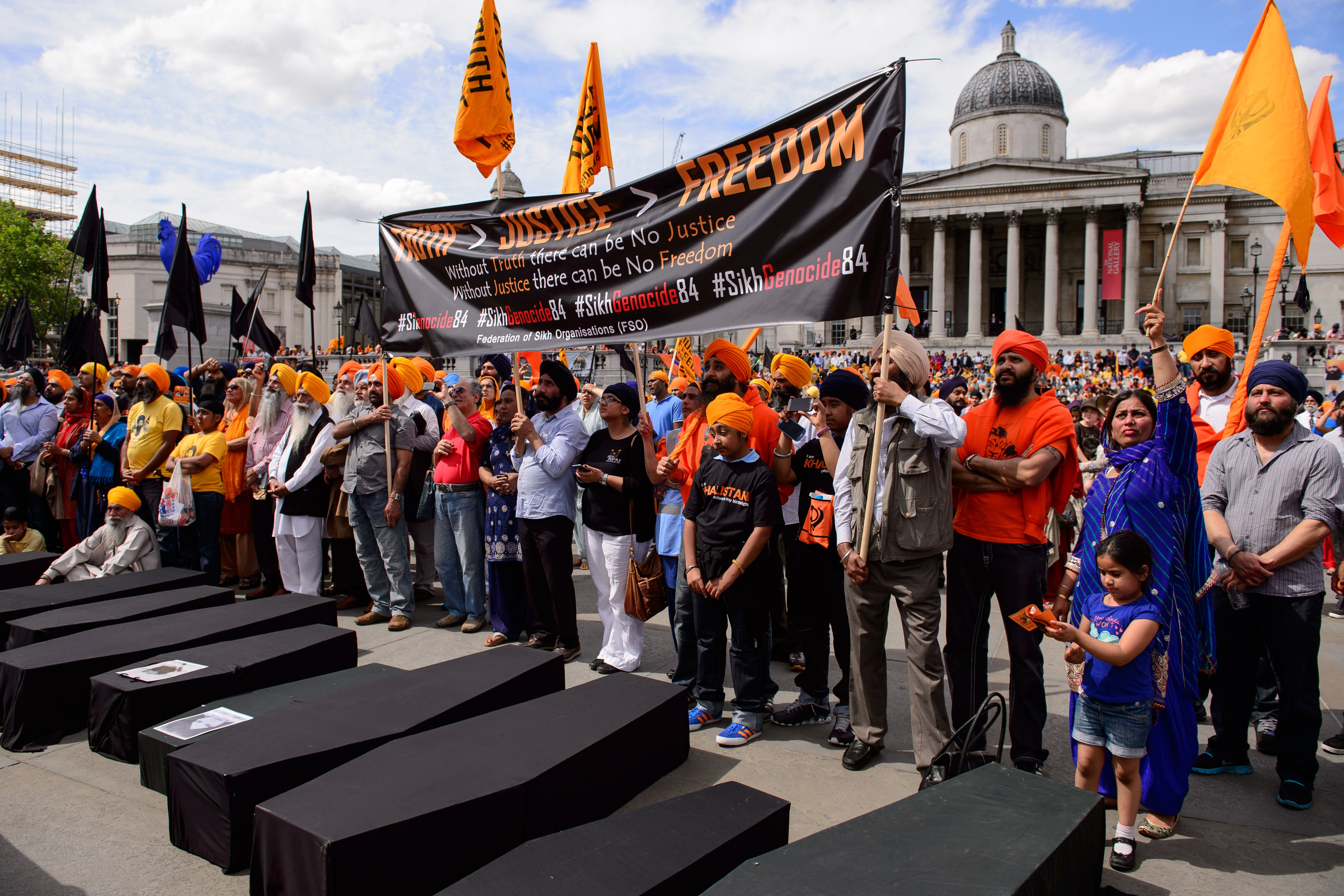 Members of the Sikh community hold aloft a banner calling for the 1984 storming of Sikhism's holiest shrine, the Golden Temple in Amritsar, by Indian troops, to be recognised as genocide as they join a demonstration in central London on June 8, 2014, to mark the 30th anniversary of the assault known as Operation Blue Star.