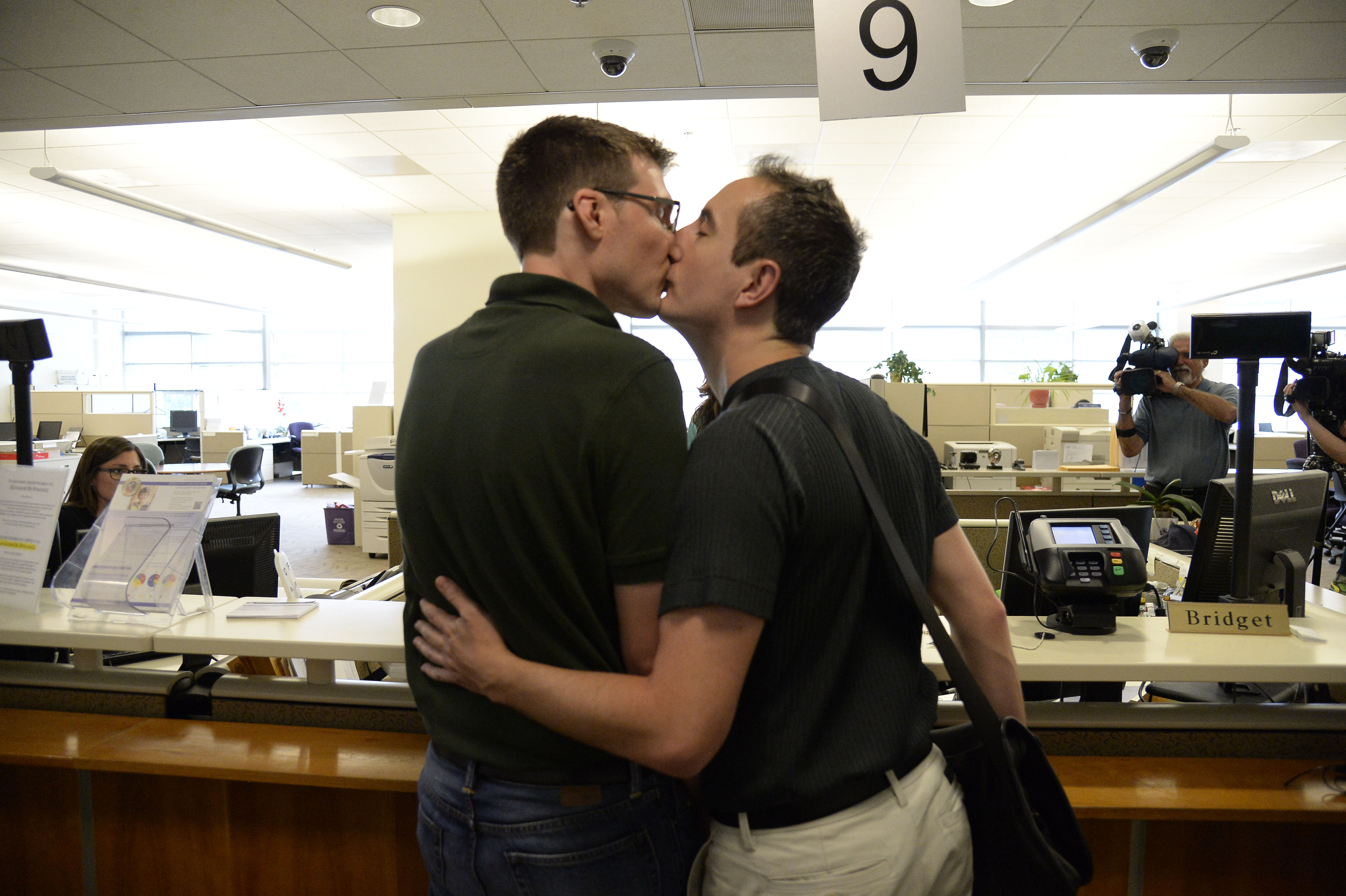 Jason Woodrich (L) and Ben Hauth share a kiss after signing their marriage license at the Denver County clerk's office where they began issuing same sex marriage licenses July 10, 2014.