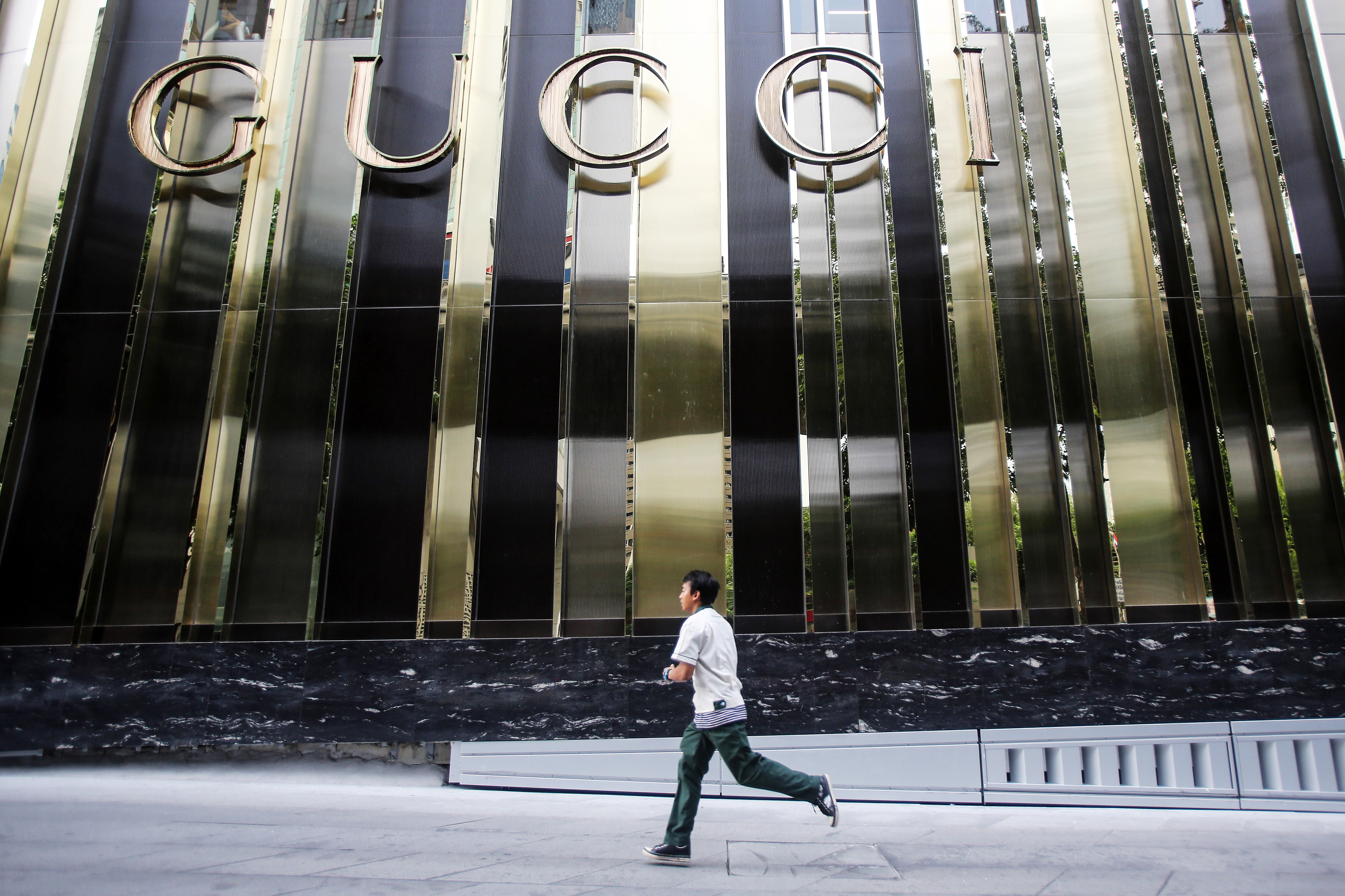 A man runs past the Gucci logo displayed outside the Central Embassy luxury mall in Bangkok on Aug. 15, 2014