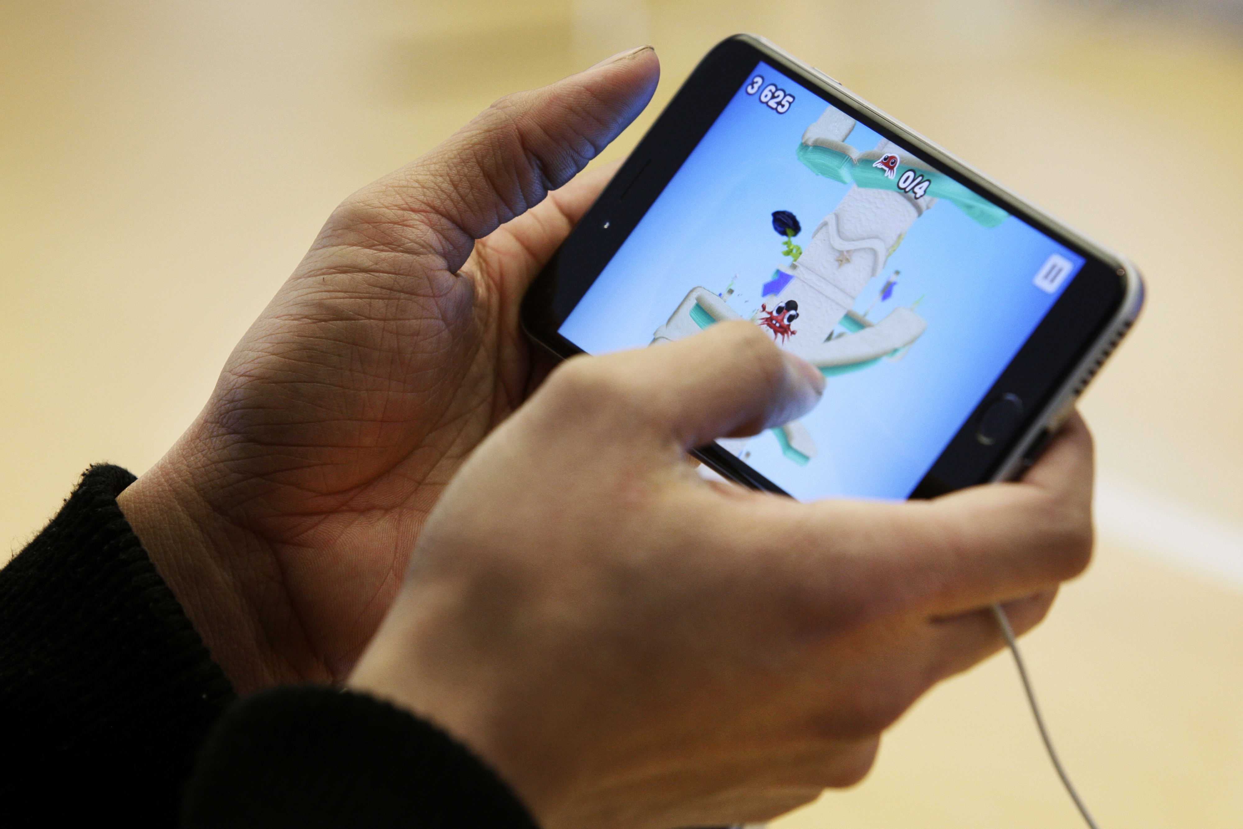 A customer plays a game on an iPhone 6 at the Apple Inc. George Street store during the sales launch of the iPhone 6 and iPhone 6 Plus in Sydney, Australia, on Friday, Sept. 19, 2014.