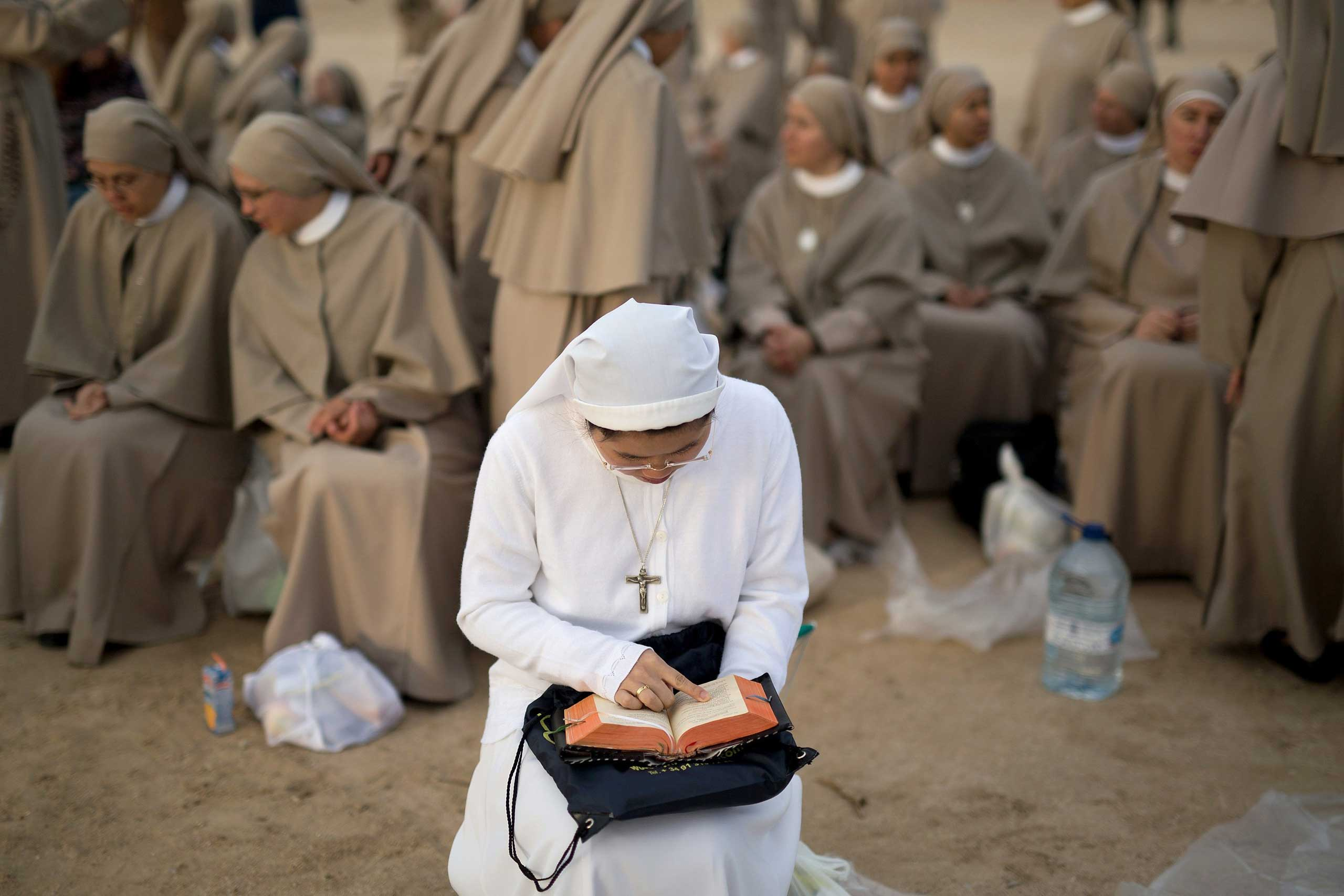 Sept. 27, 2014.  A nun reads as she waits for the start of the beatification ceremony of Opus Dei former leader Bishop Alvaro del Portillo in a huge open air mass in Madrid, Spain.