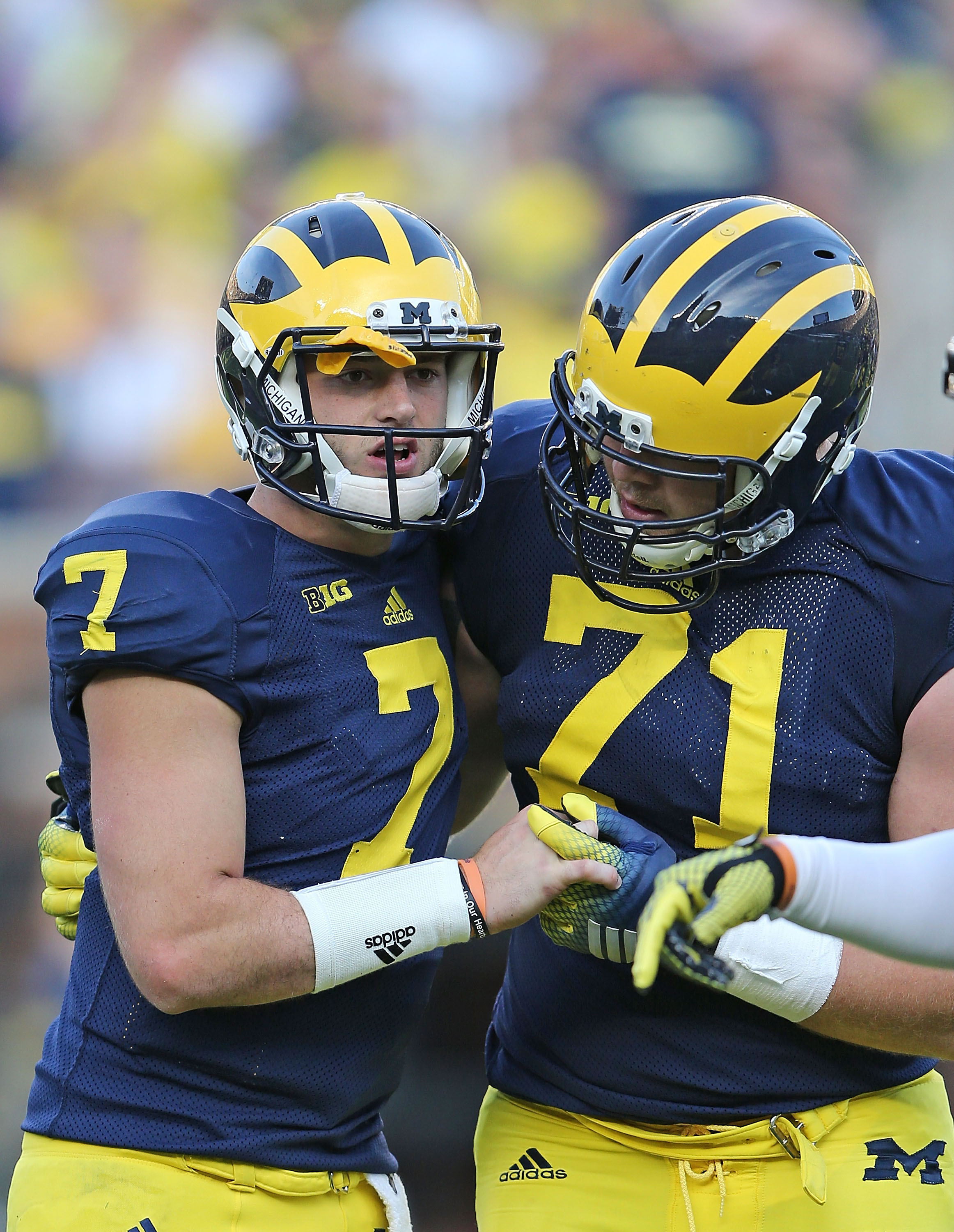 Quarterback Shane Morris (#7) of the Michigan Wolverines is helped off the field by Ben Braden (#71) during the fourth quarter of the game against the Minnesota Golden Gophers on Sept. 27, 2014, at Michigan Stadium in Ann Arbor, Mich.