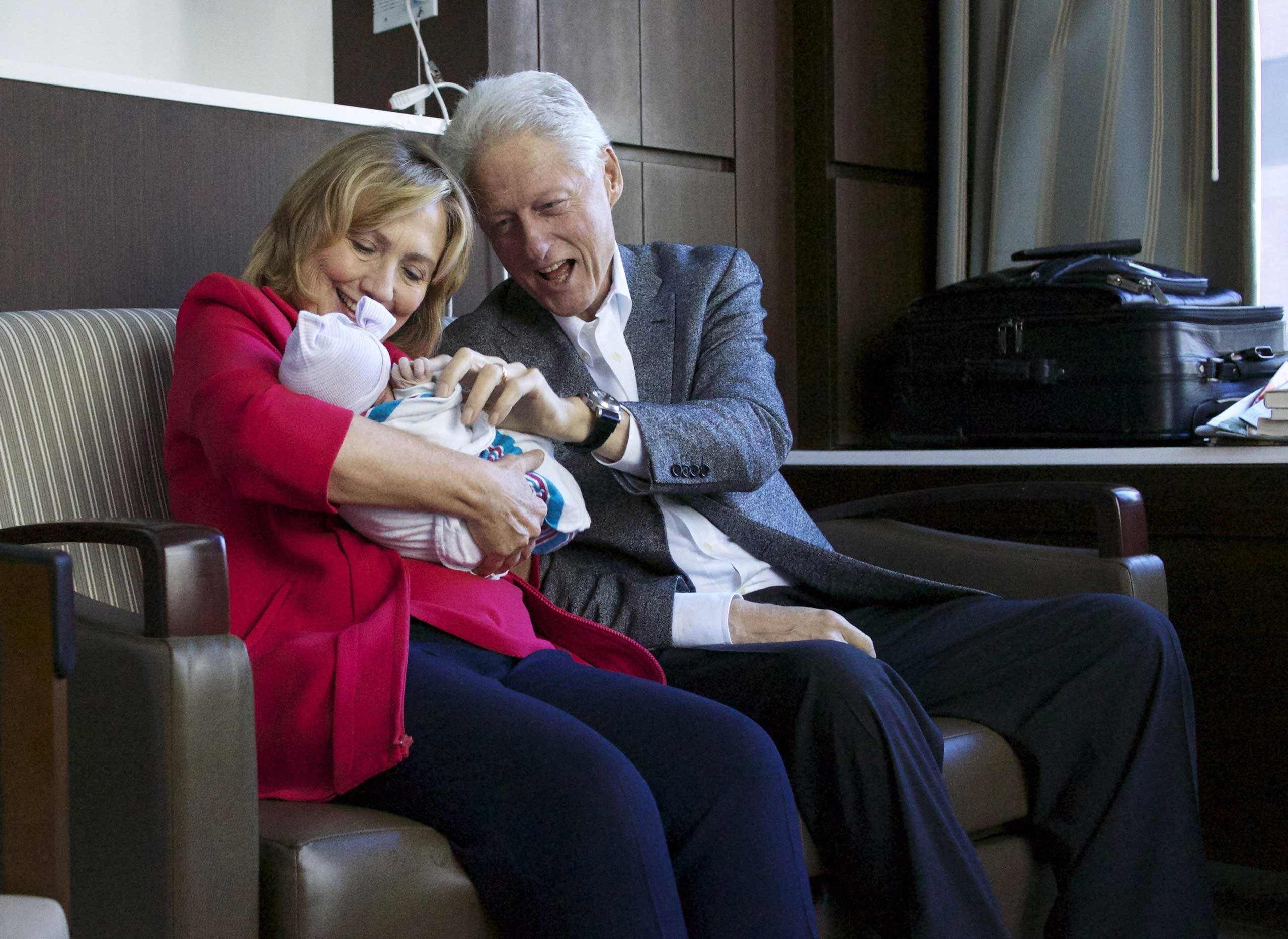 Sept. 27, 2014. In a handout from the Office of President Clinton, former Secretary of State Hillary Clinton (L) and fomer U.S. President Bill Clinton (R) hold their grandchild Charlotte Clinton Mezvinsky at Lenox Hill Hospital in New York City.