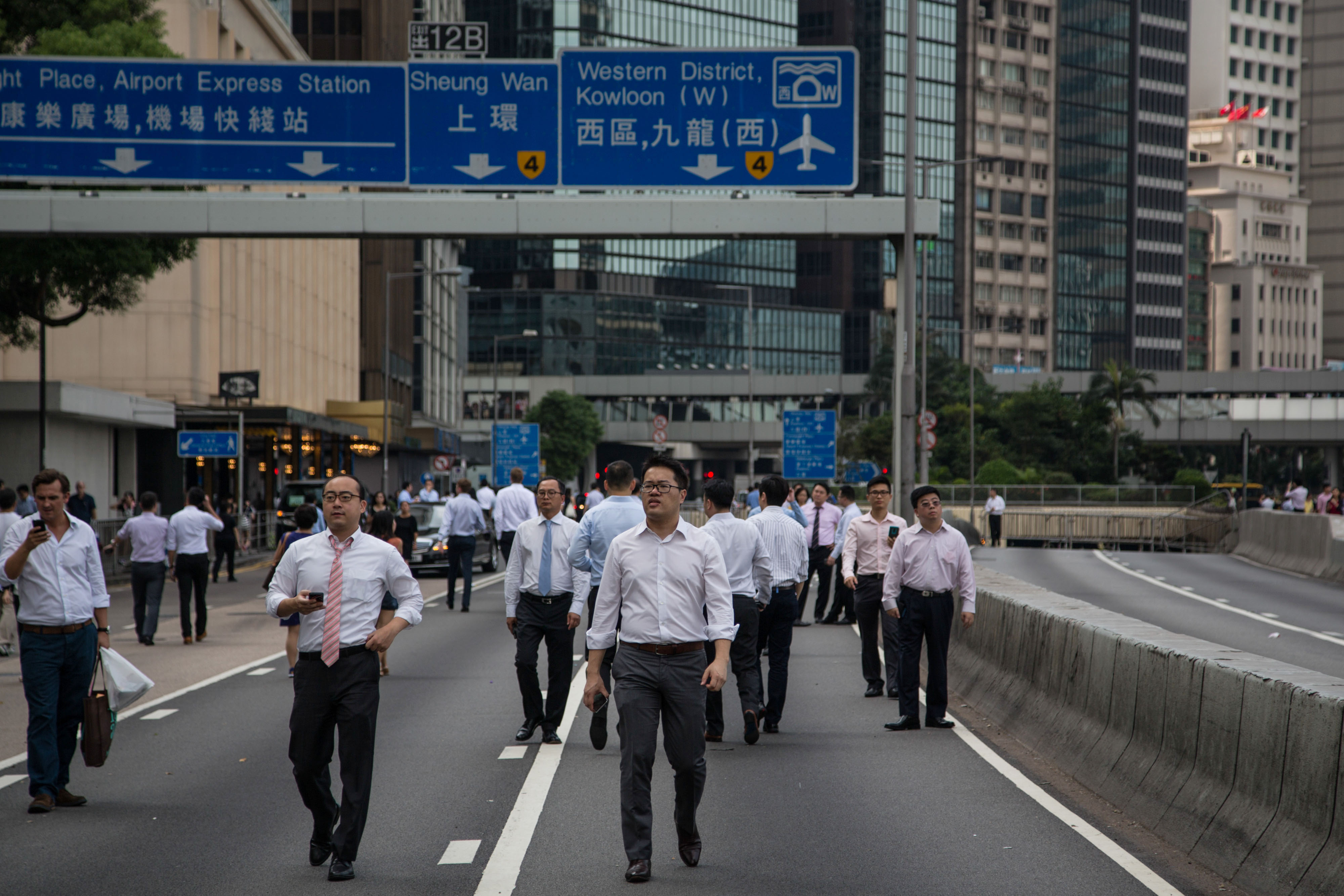 Office workers walk through streets closed by protesters in the business district of Central in Hong Kong, China, on Monday, Sept. 29, 2014.