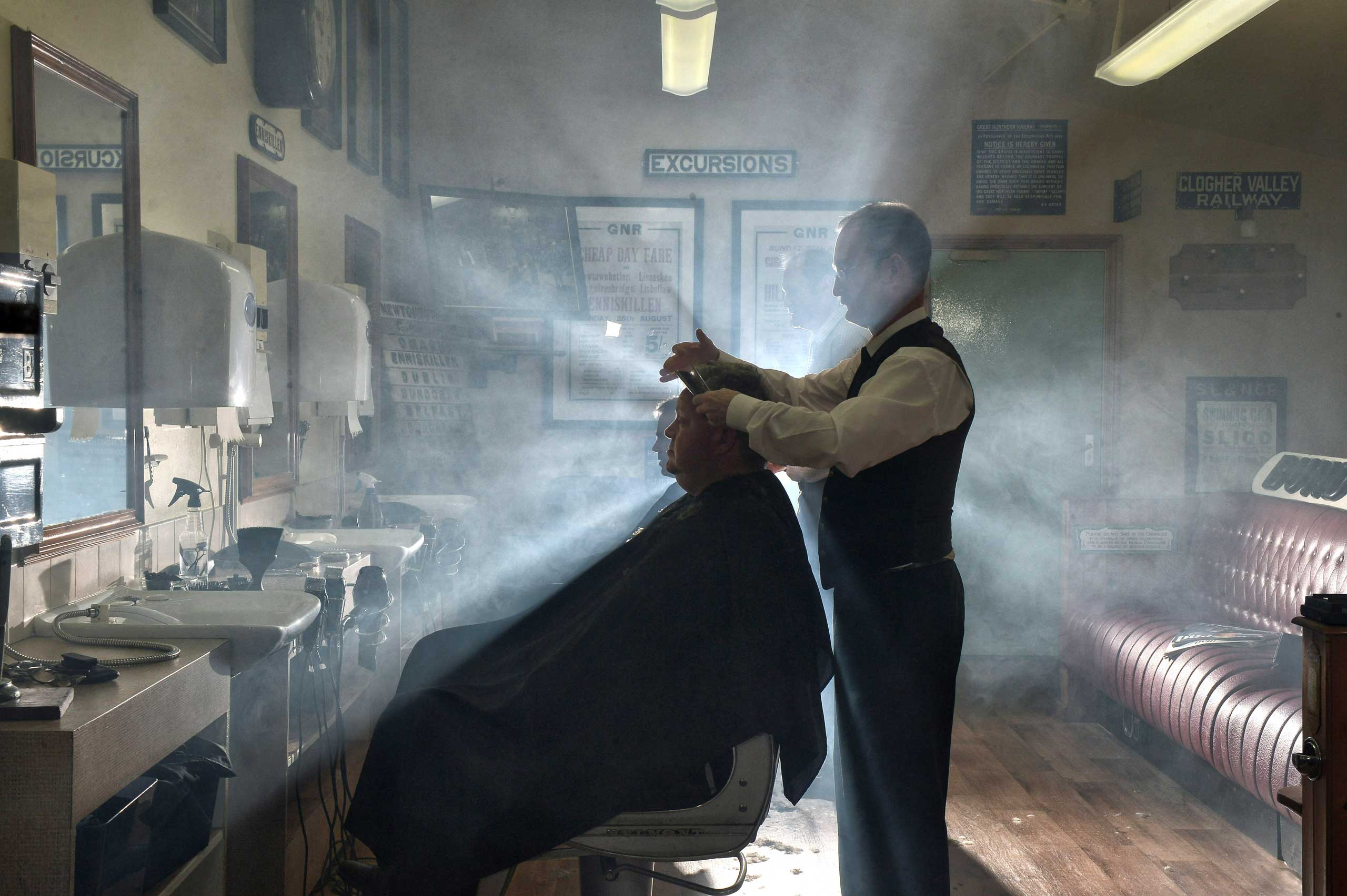 Sept. 29, 2014. A customer of the Headhunters Barber Shop and Railway Museum gets a hair and from station master Nigel Johnston in Enniskillen, Northern Ireland. Established in 2002, with the help of former railway employees and enthusiasts, the museum is run by three brothers, Selwyn, Nigel and Gordon Johnston whose purpose whilst operating a busy hairdressing service from within the museum is to collect, preserve, and interpret local railway heritage for the benefit of the community. Visitors and customers both start their journey at the reconstructed Railway Booking Office where the ticket collector invites you to step on board and enjoy the evocative nostalgia and artefacts associated with the railways which operated throughout Fermanagh and the Border Counties until their closure in 1957.