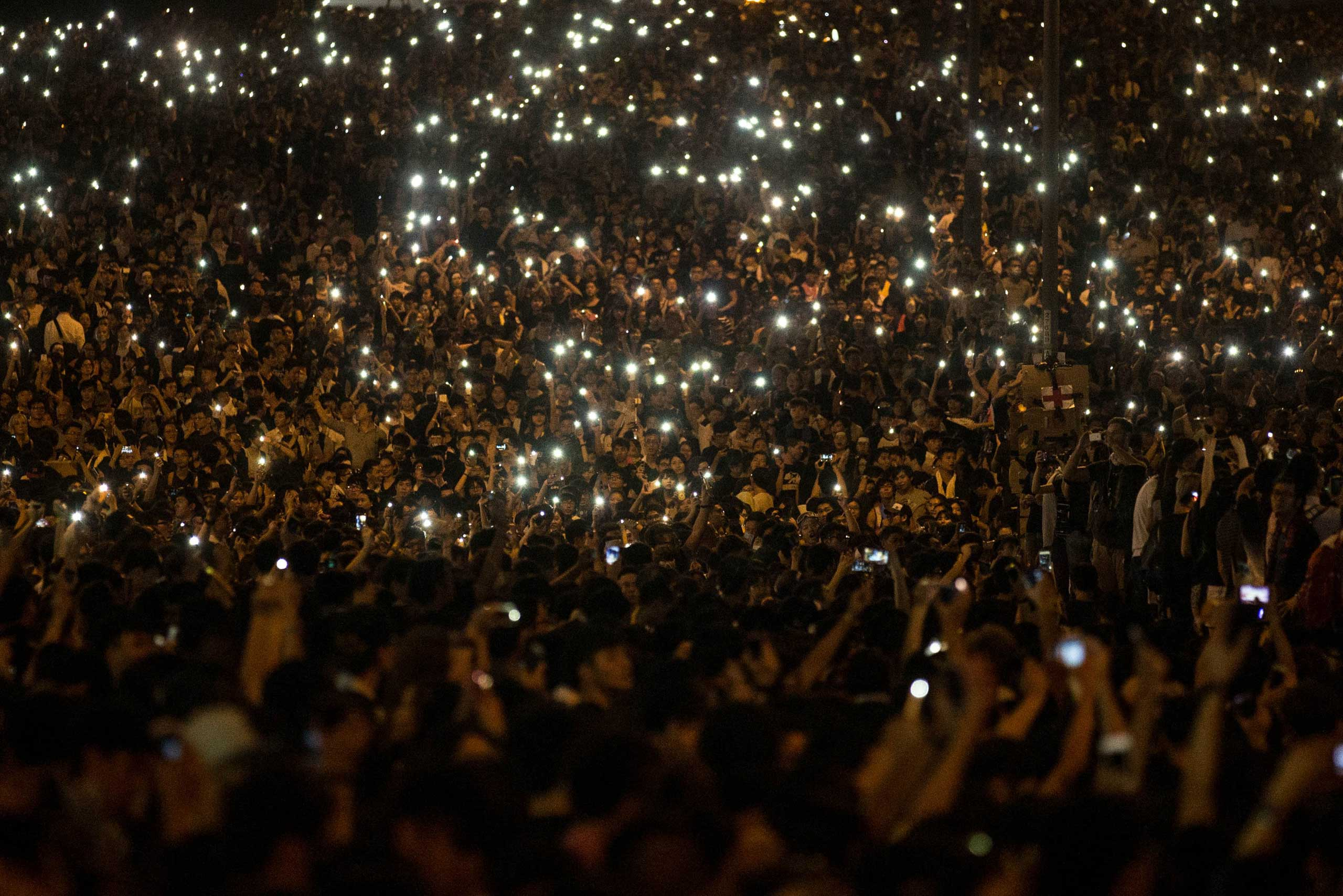 Sept. 29, 2014. Protesters wave their cell phones in the air in the streets outside the Hong Kong Government Complex in Hong Kong. Thousands of pro democracy supporters have remained in the streets of Hong Kong for another day of protests.