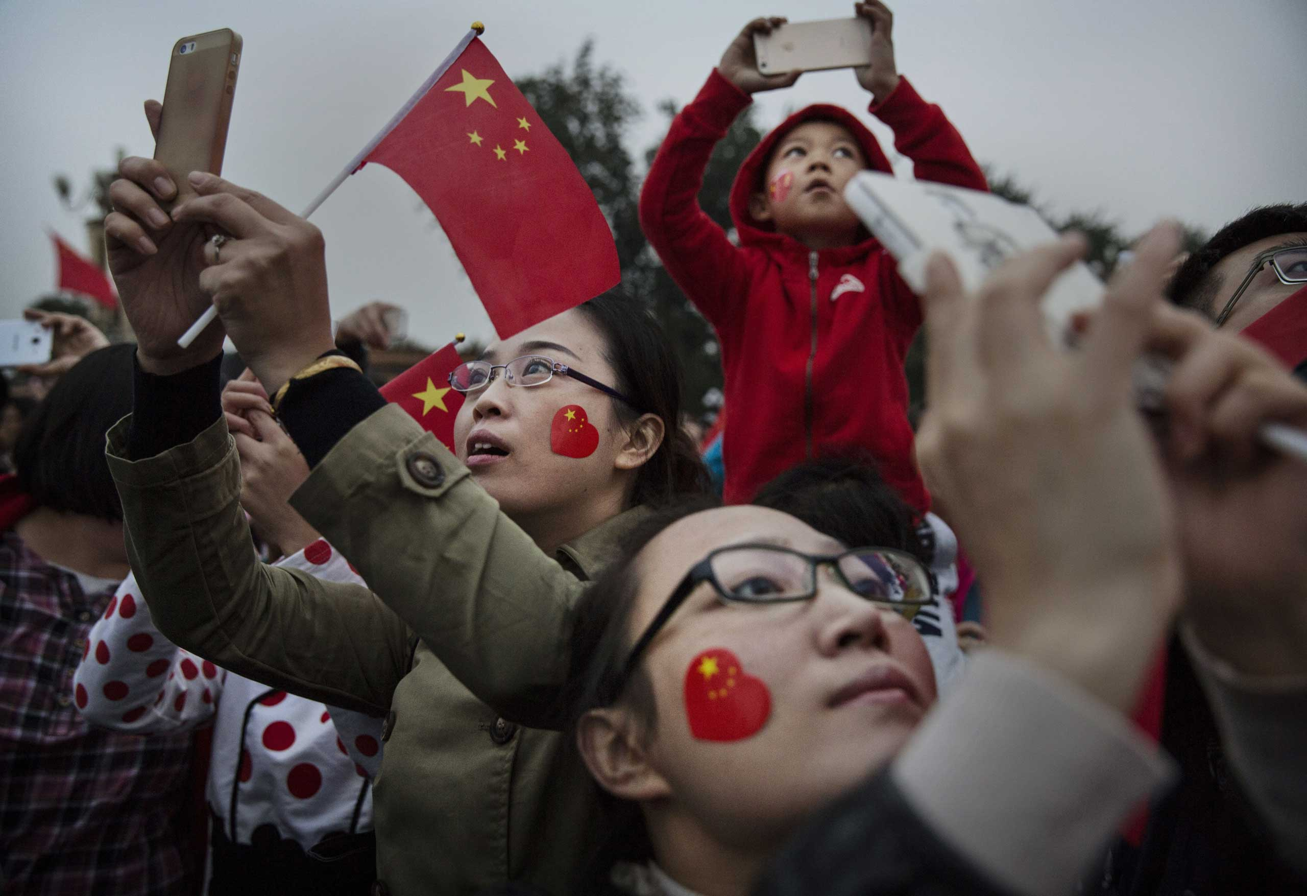 Oct. 1, 2014. Chinese tourists take pictures near Tiananmen Square on the 65th National Day in Beijing, China. The day marks the founding of the People's Republic of China on October 1, 1949.