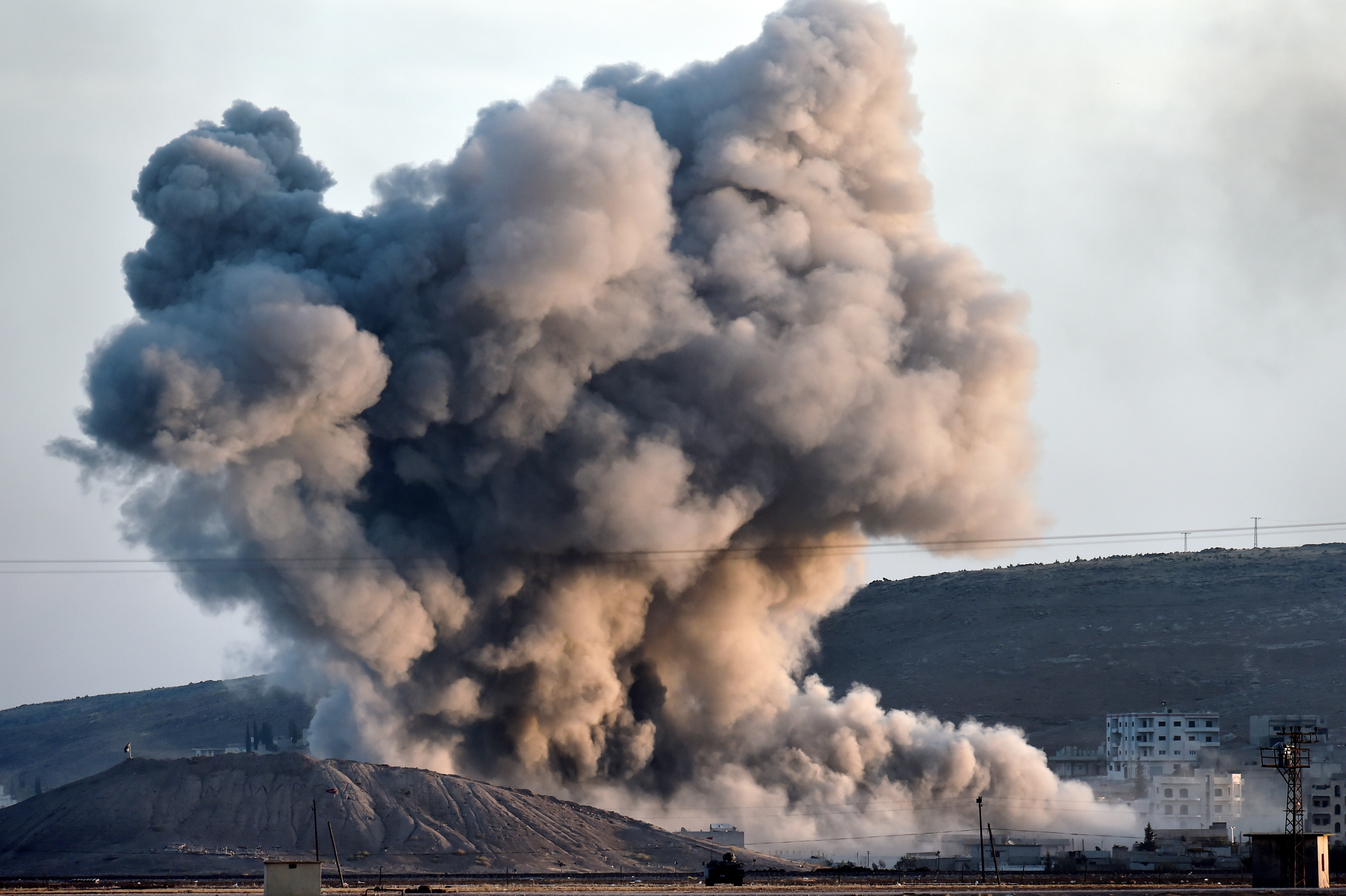 An allied air strike hits a hill in Kobani Wednesday near where ISIS fighters had planted their flag.