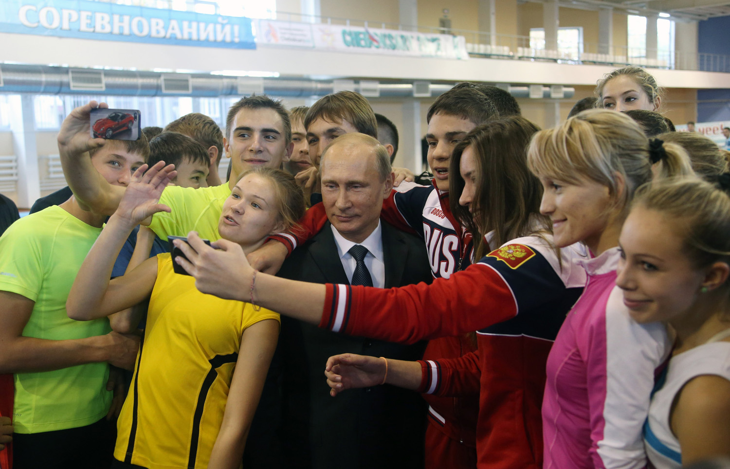 Russian President Vladimir Putin poses for a photo surrounded by teenage athletes as he attends a meeting with officials, ministers and governors on sport development in Cheboksary, Russia on Oct. 9, 2014.