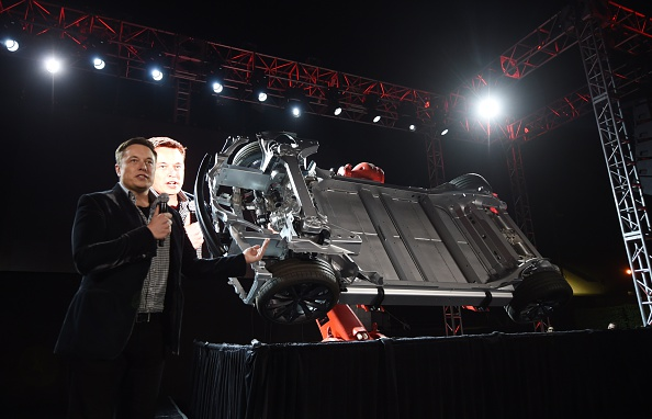 Tesla founder and chief executive Elon Musk unveils a new dual-engine chassis at the Hawthorne Airport in Los Angeles on Oct. 9, 2014