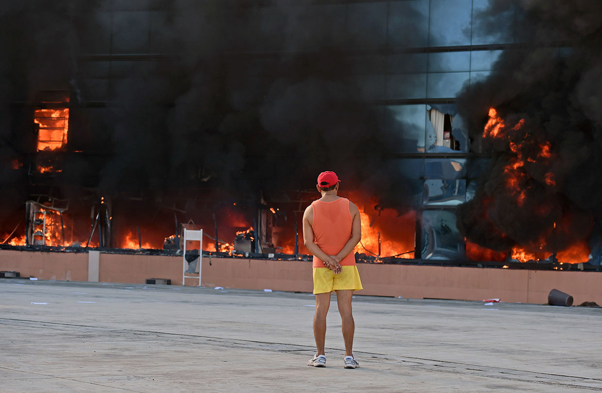 A man stares at the blazing government headquarters in Chilpancingo, in Mexico's Guerrero state, on Oct. 13, 2014, after protesters set it on fire during demonstrations demanding the return of the 43 students still missing since an attack by rogue officers earlier this month