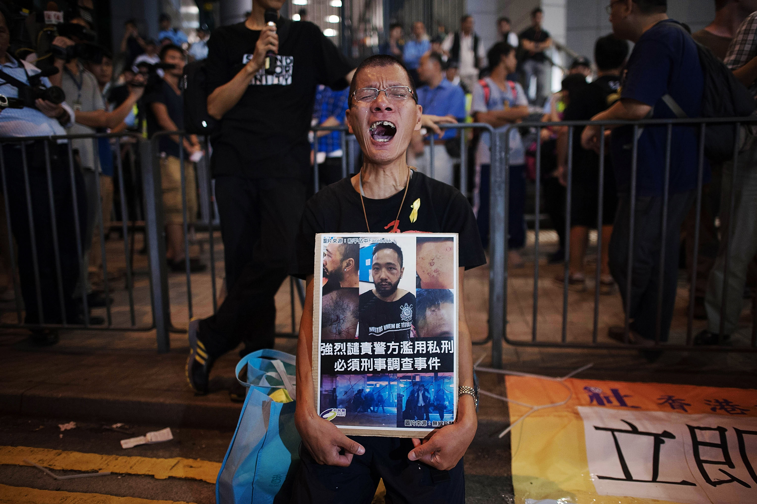 A man, a friend of activist Ken Tsang, who got kicked and beaten by police officers, shouts as he kneels on a street outside of the Hong Kong Police Headquarters in Wan Chai district in Hong Kong on Oct. 15, 2014