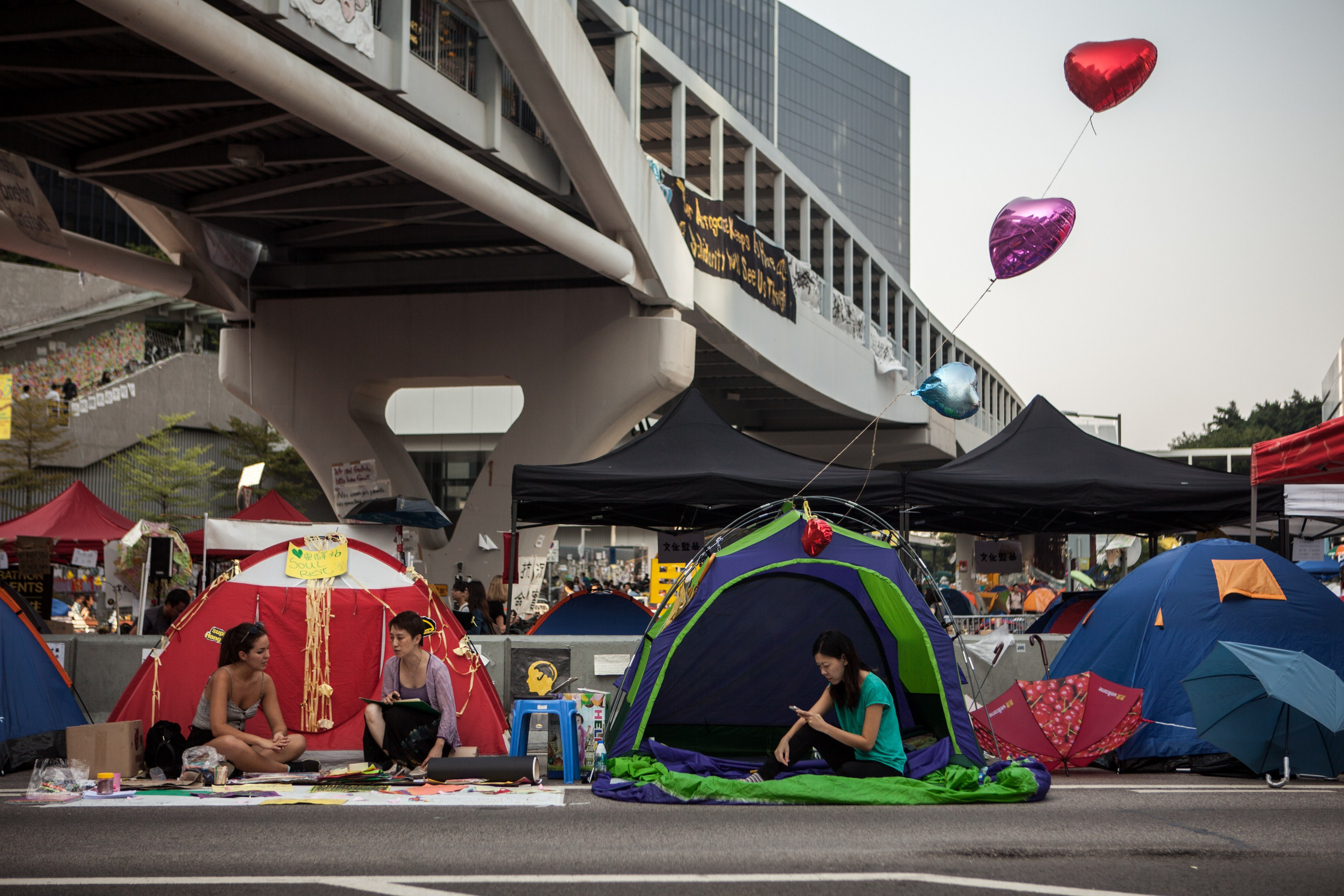 Members of the Occupied movement rest in their tents on a highway blocked by protestor barricades in the Admiralty district of Hong Kong on October 16, 2014.