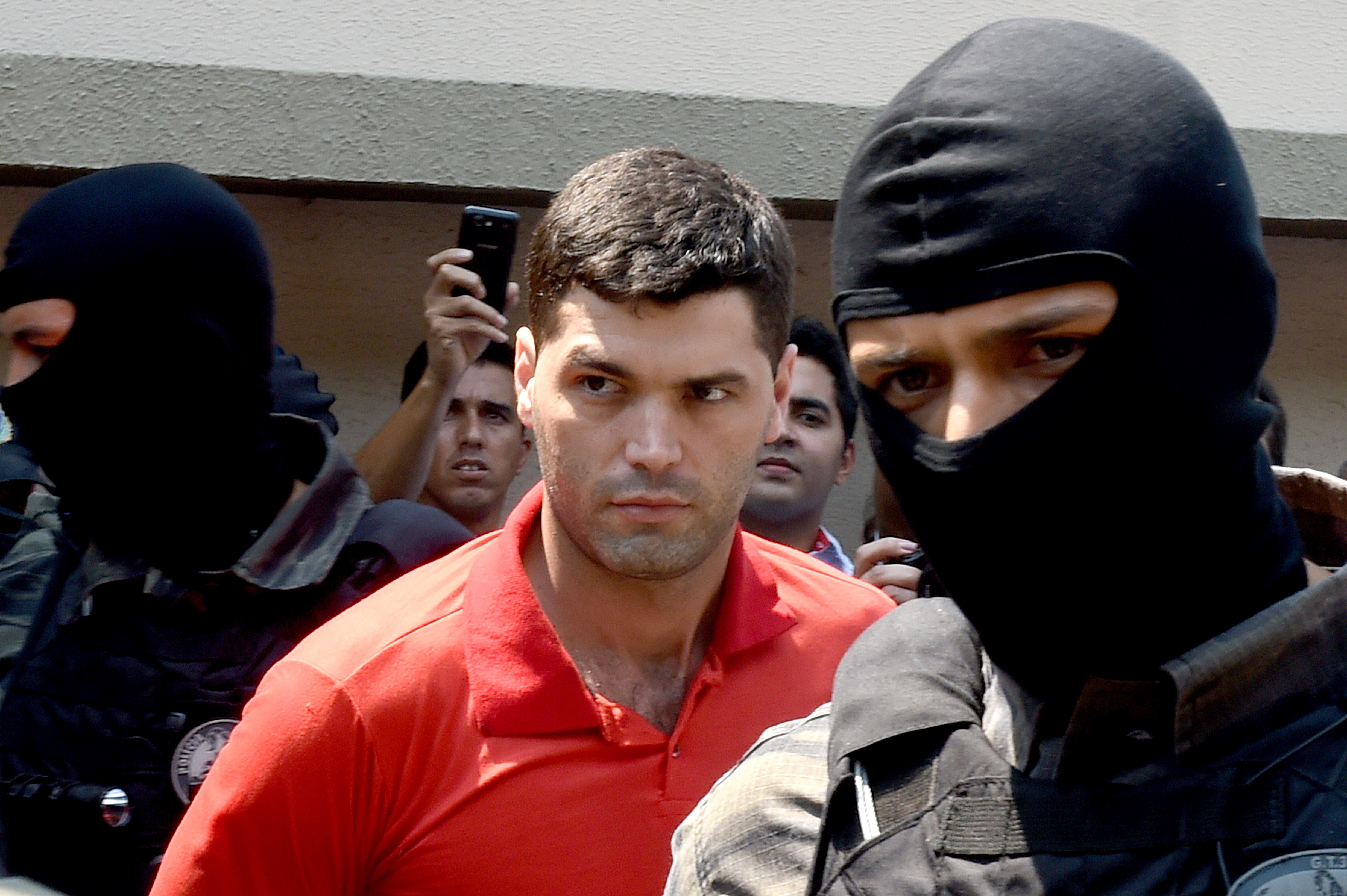 Alleged serial killer Tiago Gomes da Rocha, center, suspected of killing 39 people, is escorted by police officers at the Department of Security, a day after his arrest, in Goiania, state of Goias, Brazil, on Oct. 16, 2014.