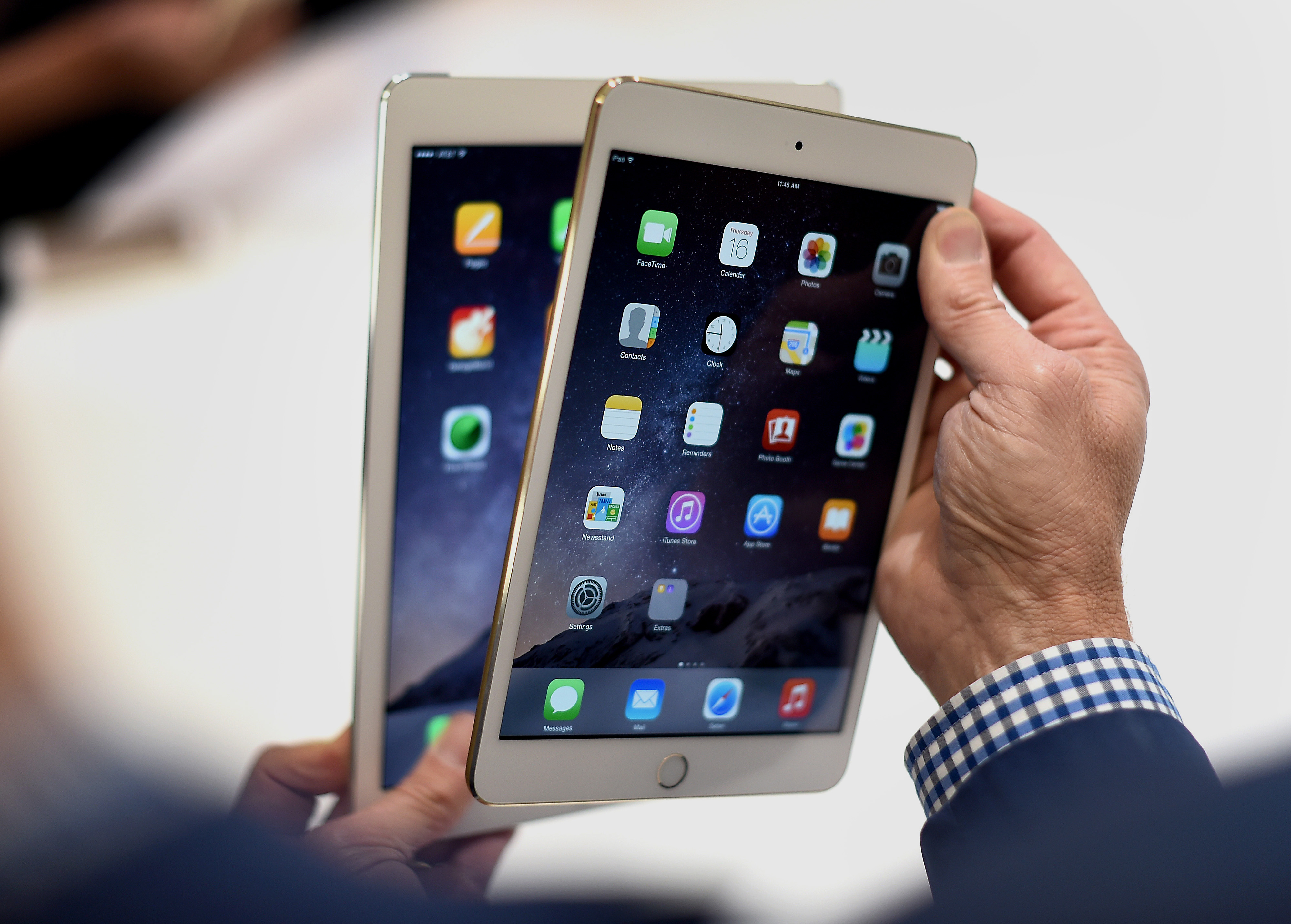A member of the media displays an Apple Inc. iPad Mini 3, left, and iPad Air 2 for a photograph after a product announcement in Cupertino, California, U.S., on Thursday, Oct. 16, 2014.