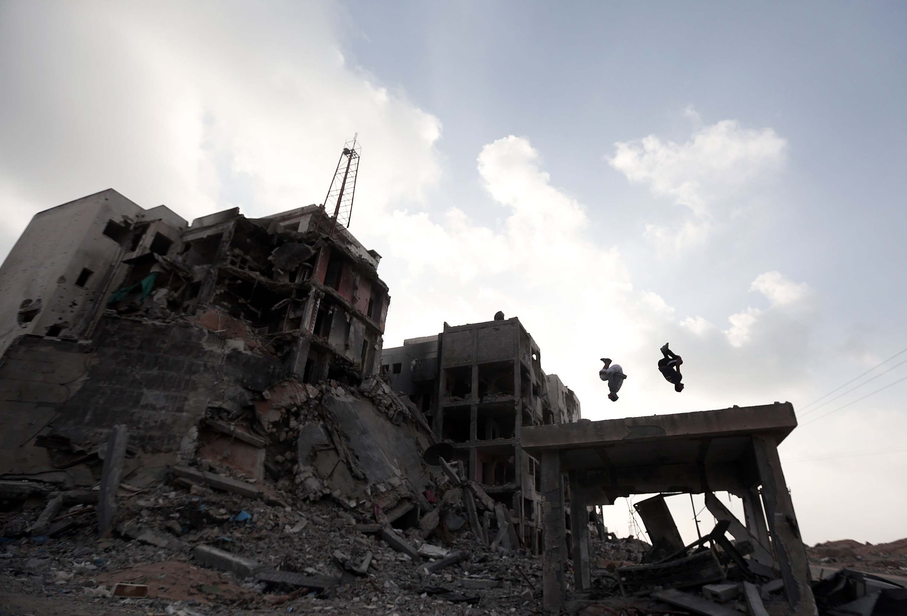 Palestinian boys practice parkour skills amid the ruins of buildings, which were destroyed by Israeli offensives in Beit Lahia town of Gaza on Oct. 18, 2014.
