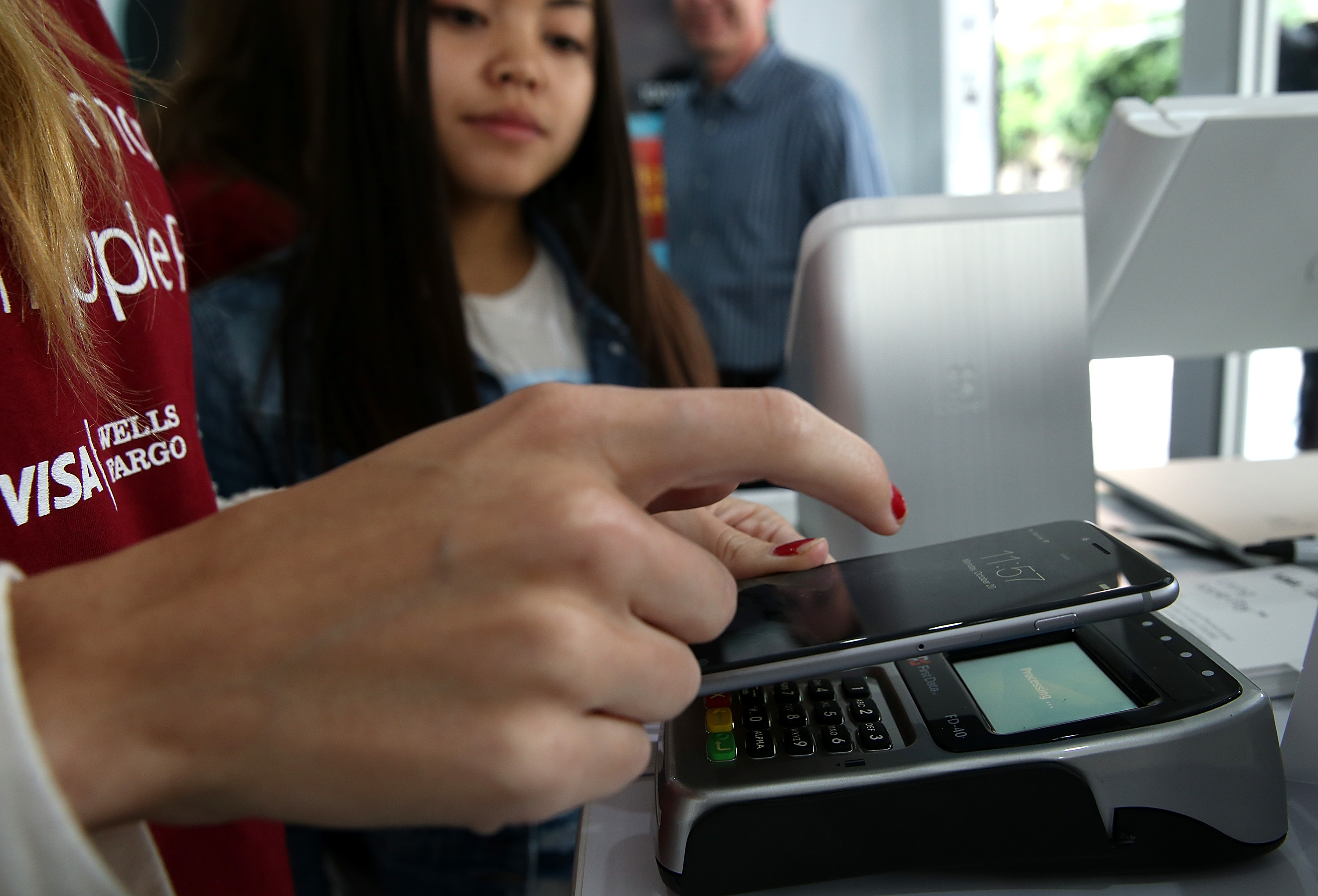 A worker demonstrates Apple Pay inside a mobile kiosk sponsored by Visa and Wells Fargo to demonstrate the new Apple Pay mobile payment system on October 20, 2014 in San Francisco City.