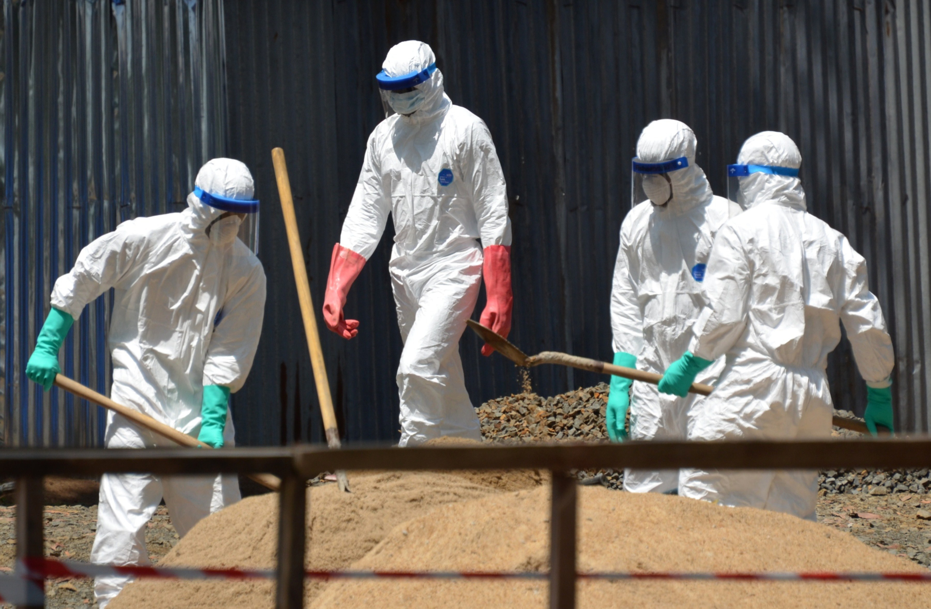 Health workers from the Liberian Red Cross wear protective gear as they shovel sand which will be used to absorb fluids emitted from the bodies of Ebola victims in front of the ELWA 2 Ebola management center in Monrovia on October 23, 2014.