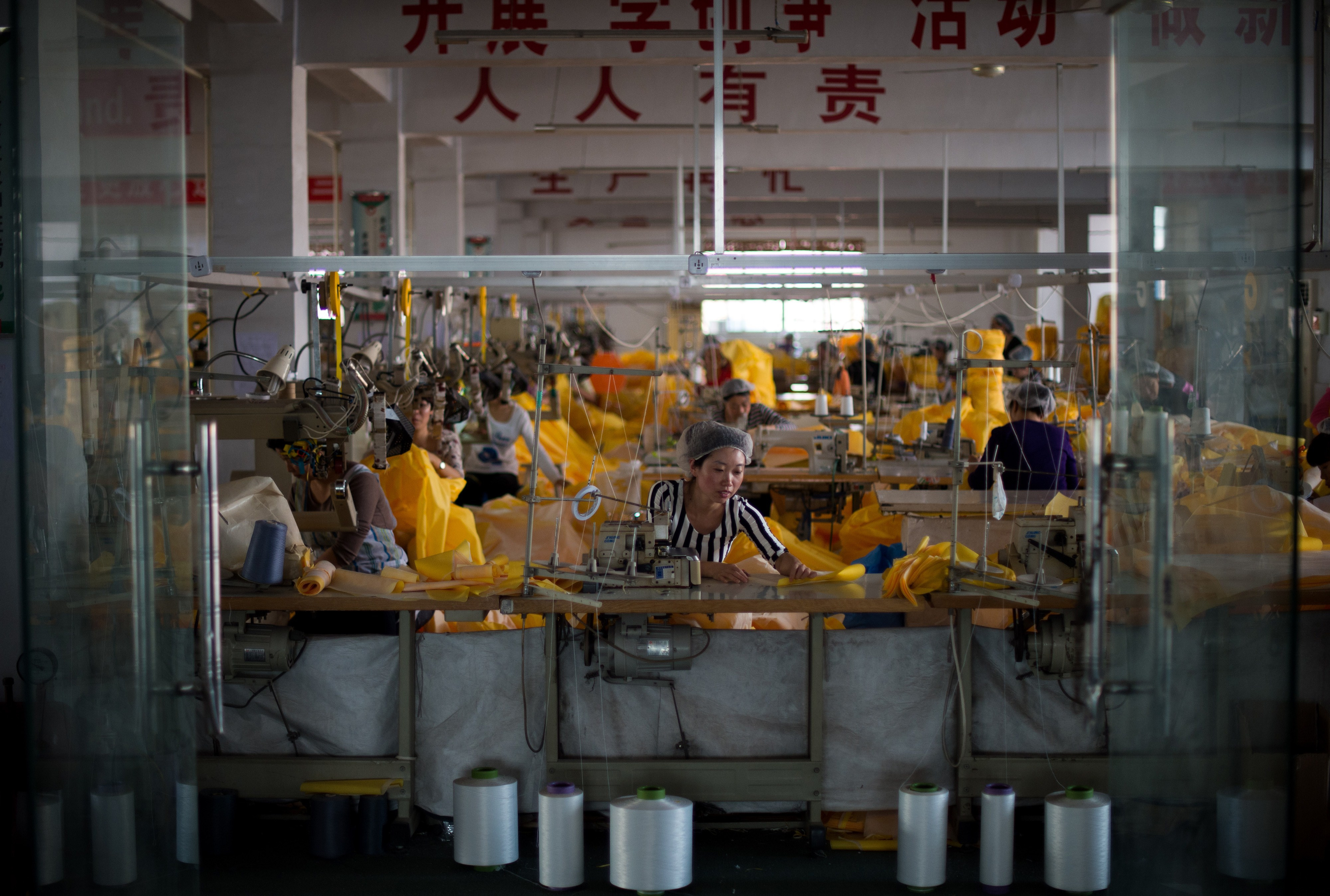 Oct. 24, 2014. Women work on the CT1SL428, a protective suit for use in handling people infected with the Ebola virus, in a sewing room of Lakeland Industries Inc. in Anqiu, some 500 kilometers south of Bejing, China.