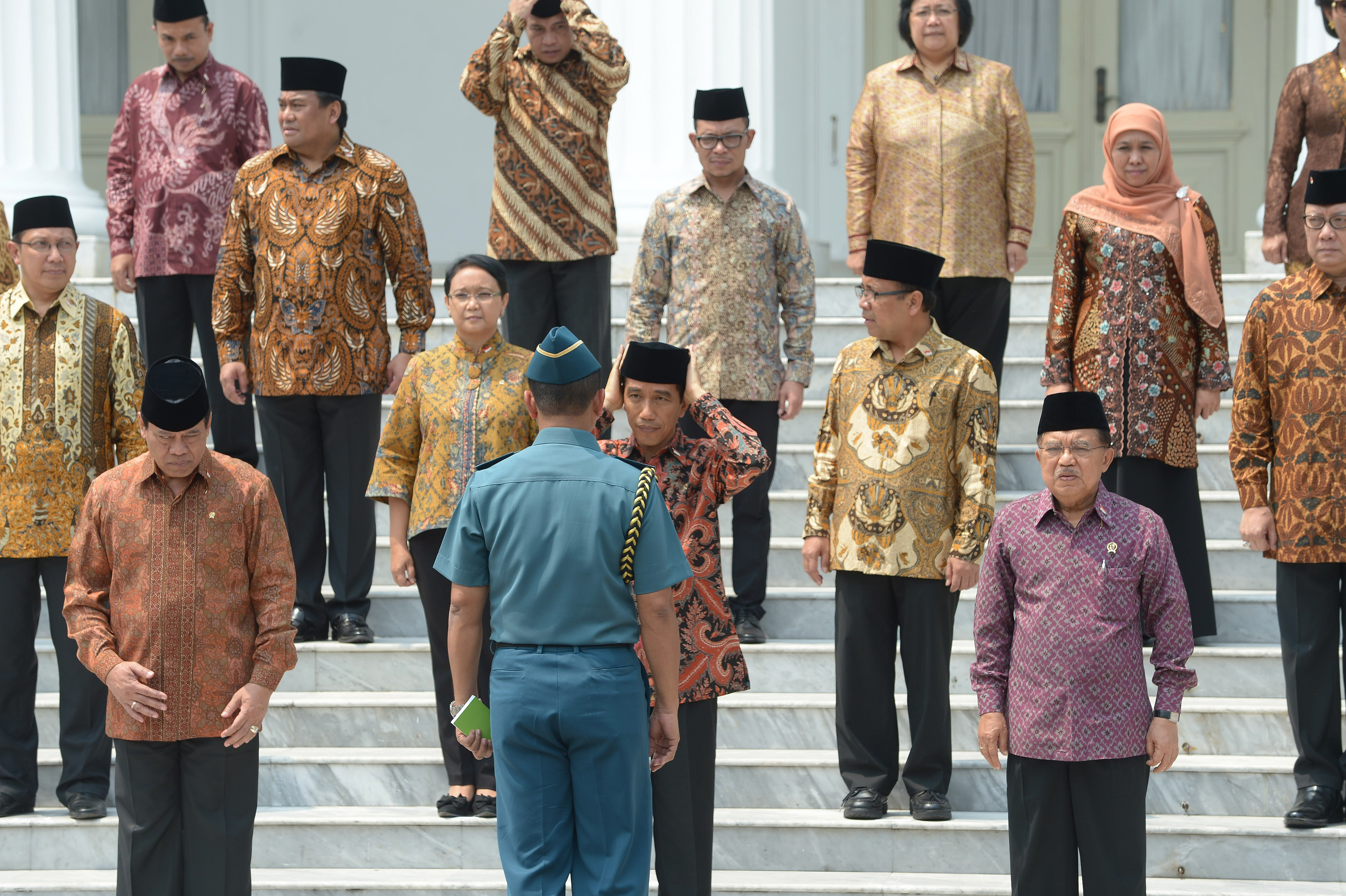 Indonesian President Joko Widodo, center, adjusts his cap next to Vice President Jusuf Kalla, front right, and surrounded by members of his new Cabinet at the presidential palace in Jakarta on Oct. 27, 2014
