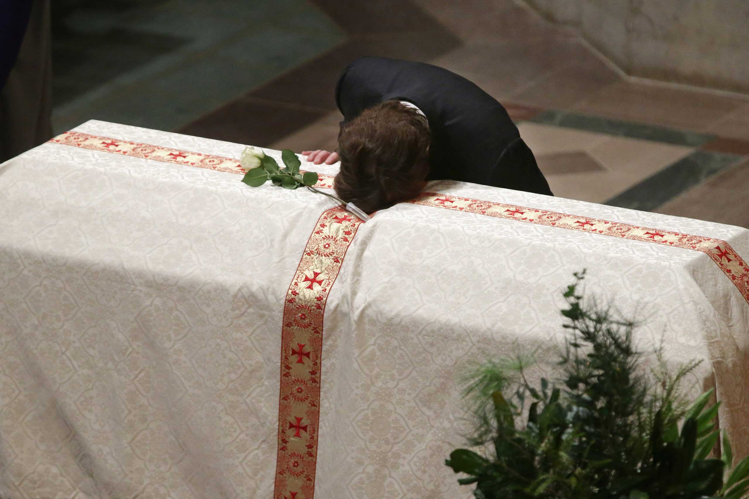 Oct. 29, 2014. Quinn Bradlee puts his head on the casket of his father and former Washington Post Executive Editor, Ben Bradlee, at the Washington National Cathedral in Washington, D.C.