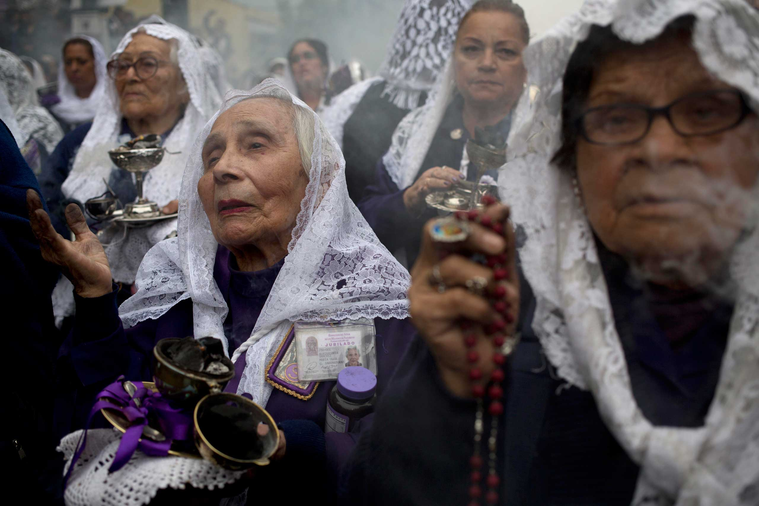 Oct. 18, 2014. Women burn incense as the image of the Lord of Miracles, the capital city's patron saint, is carried behind them in Lima, Peru. The Lord of Miracles is a 17th century mural of Jesus Christ, and the procession is the Andean country's largest Catholic event.