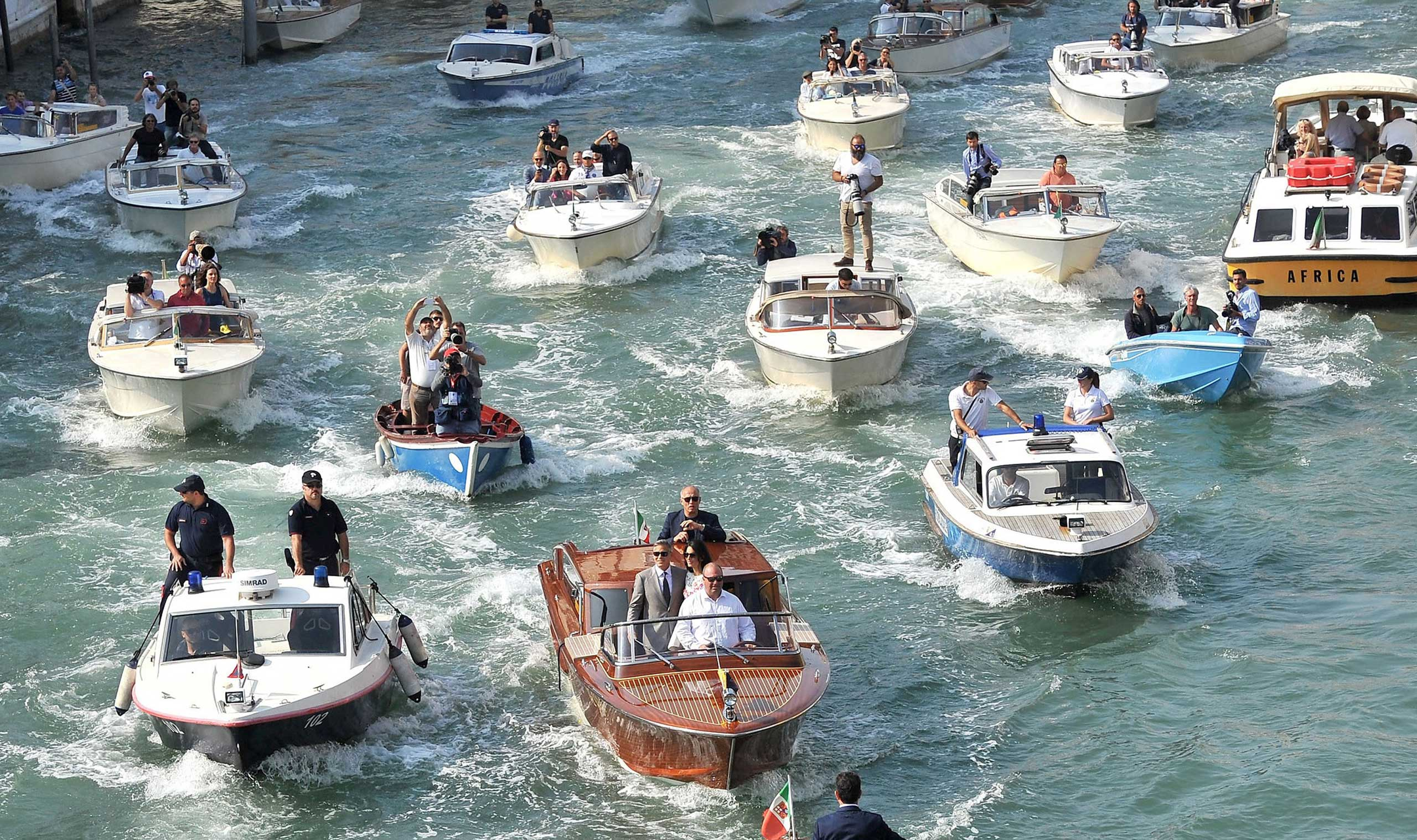 Sept. 28, 2014. The boat at center front, carrying George Clooney and his wife Amal Alamuddin is surrounded by media and security boats as they cruise the Grand Canal after leaving the Aman luxury Hotel in Venice, Italy. George Clooney married human rights lawyer Amal Alamuddin Saturday, the actor's representative said, out of sight of pursuing paparazzi and adoring crowds.