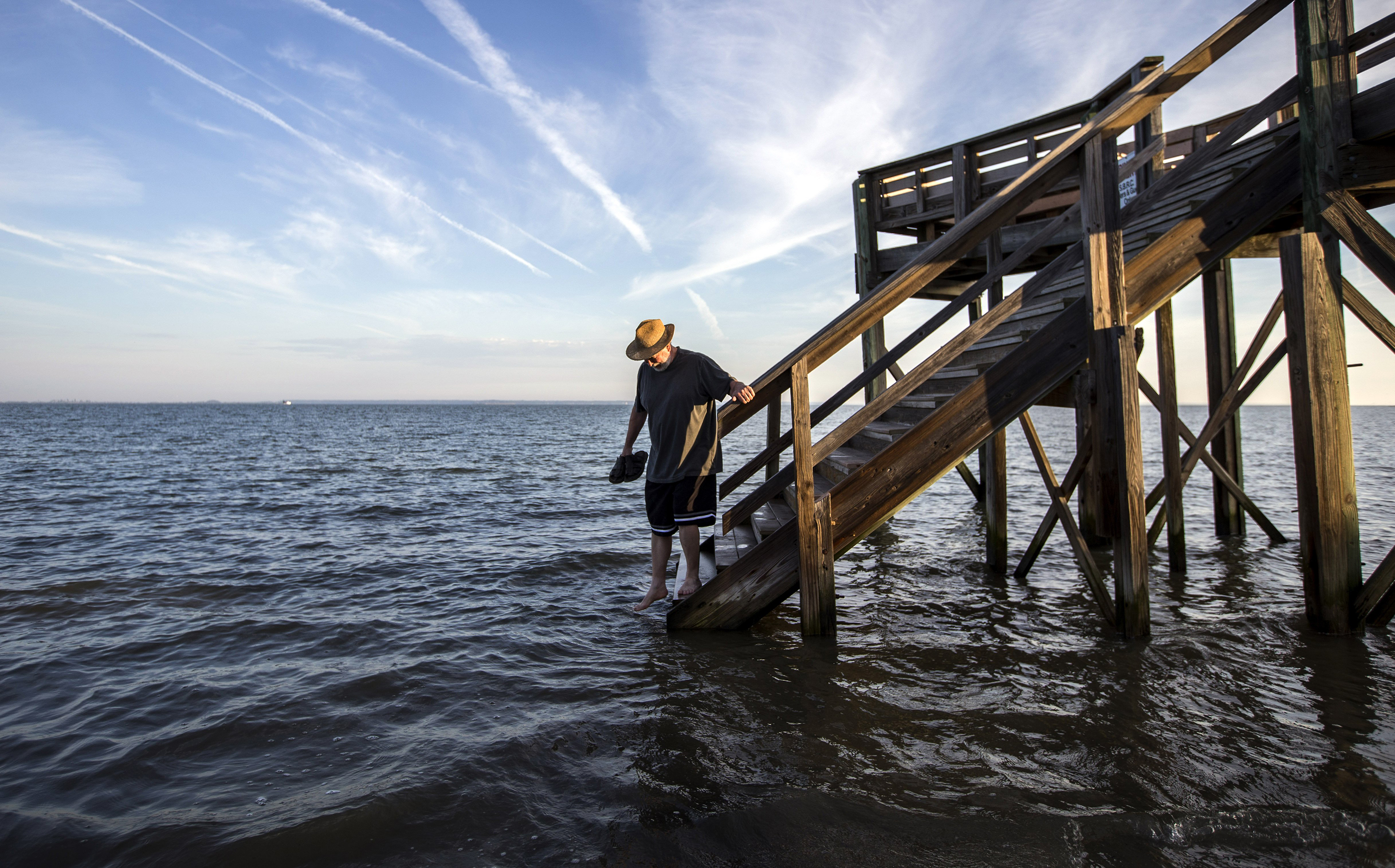 64-year-old Fran Glod of Oswego, N.Y, walks down the steps to the beach which is covered by a king tide high tide, in Tybee Island, Ga. on Oct. 9, 2014.