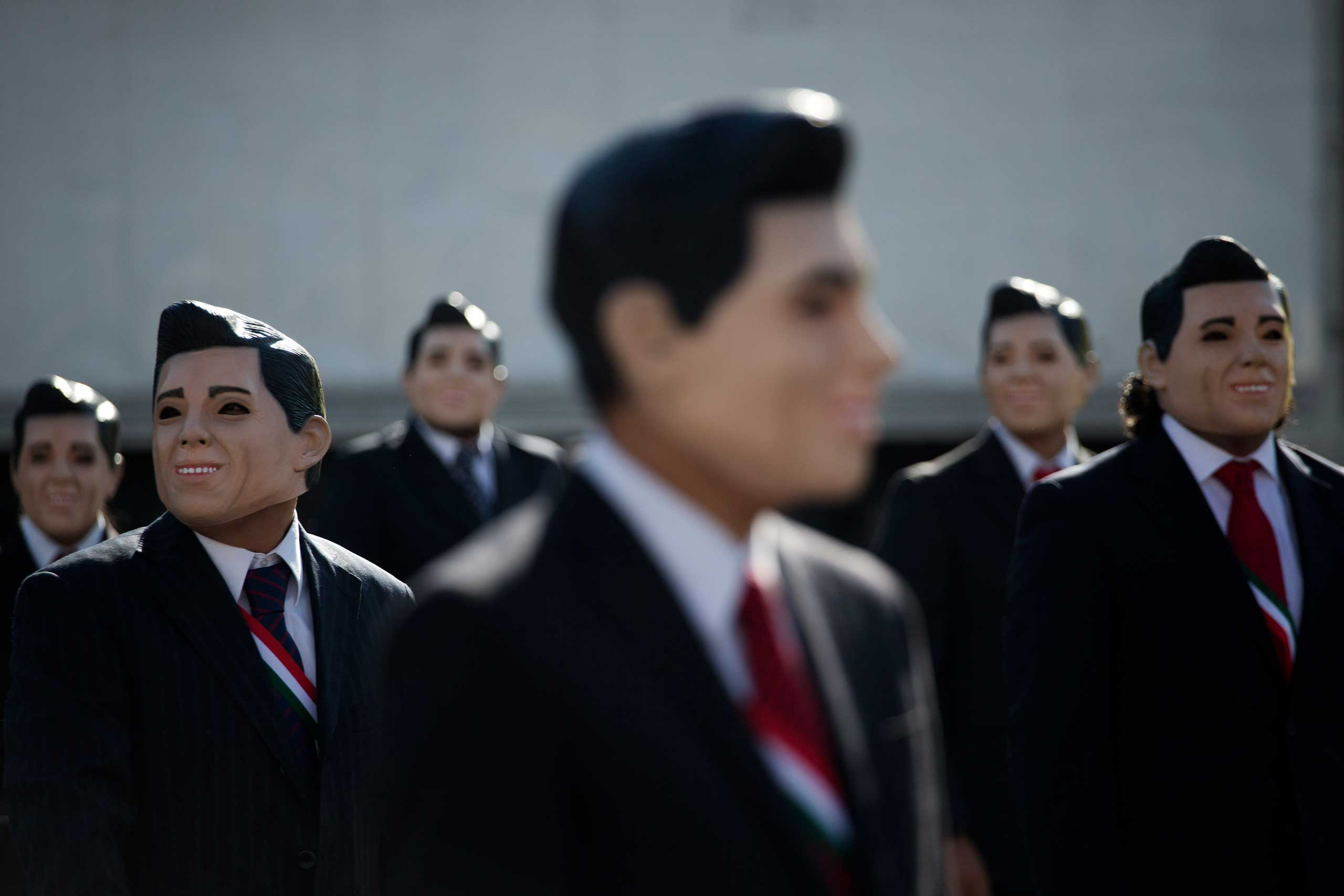 Oct. 23, 2014. Greenpeace protestors wear masks of Mexican President Enrique Pena Nieto as they demonstrate in front of the National Palace in Mexico City