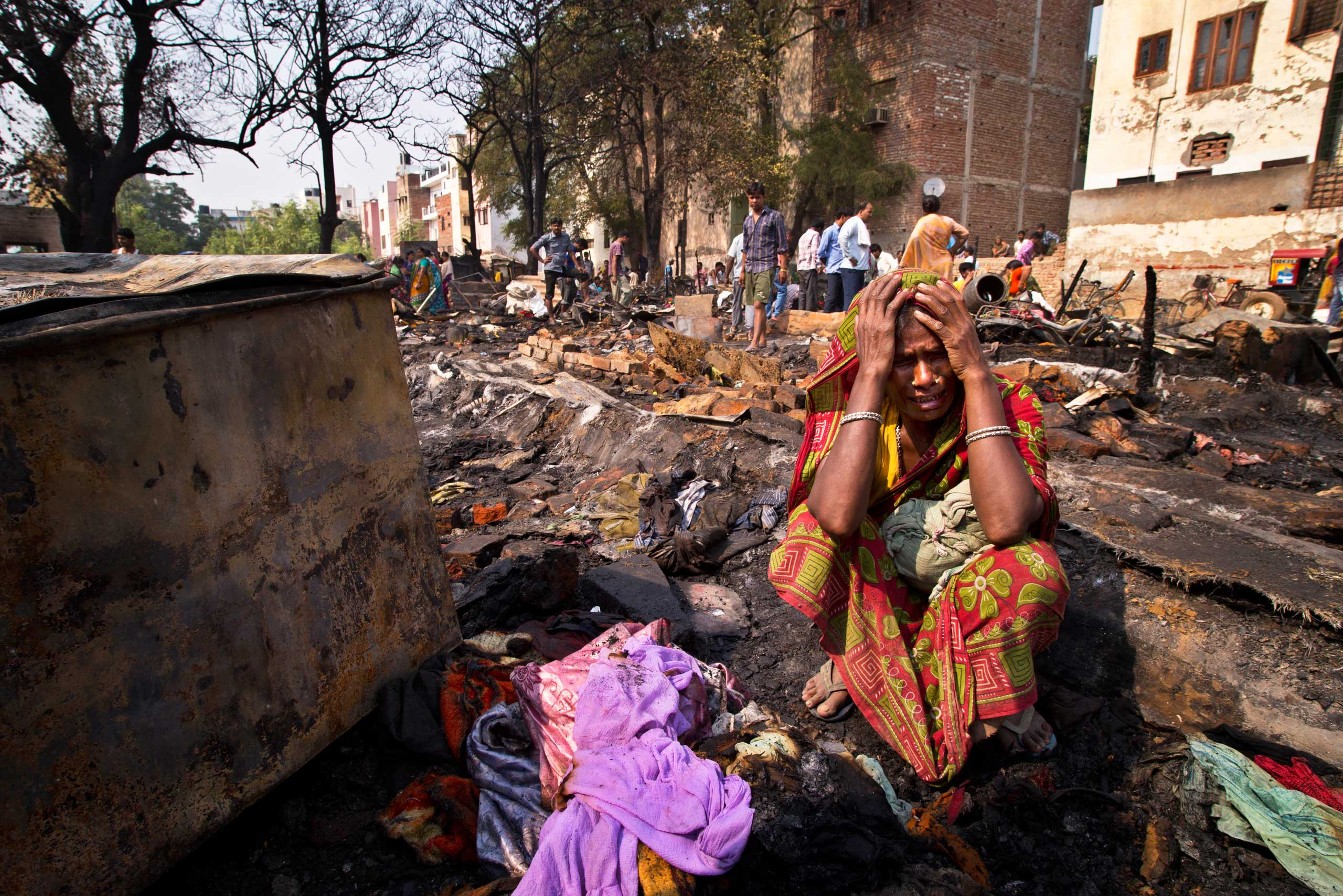 Oct. 21, 2014.  Romela Bibi cries as she holds on to a bundle of burnt money wrapped in clothes that she says amounted to nearly US$ 2,000, saved for her daughter's marriage, after fire burnt scores of houses at a slum in Gurgaon, India. There were no casualties reported. The cause of the fire is unknown.
