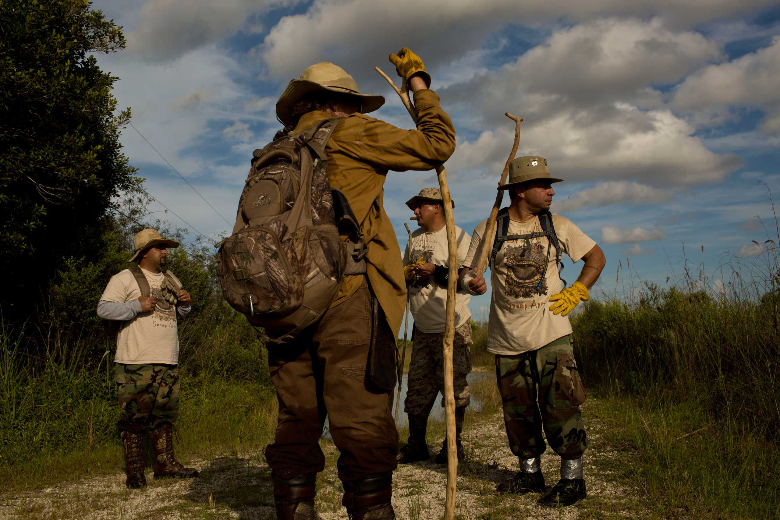"Founder of the ""Swamp Apes"" Tom Rahill speaks to veterans and volunteer members of the group during a patrol through Florida's Everglades National Park searching for invasive pythons in the Chekika area of the park on Saturday Oct. 4, 2014. From left to right are Jorge Martinez, Rahill, Jose Rodriguez, and Alex Nunez."