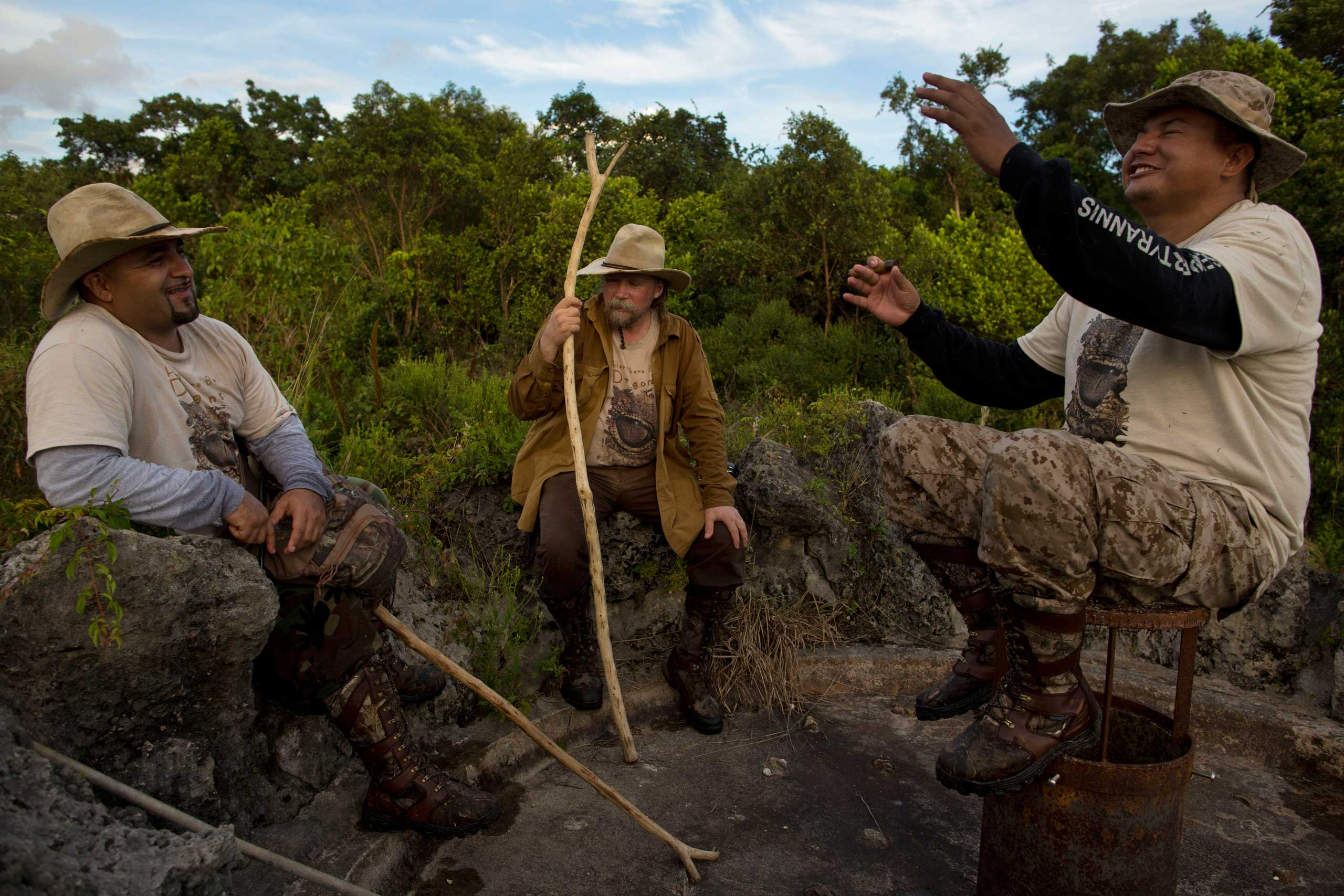 "Members of the ""Swamp Apes"" rest and tell stories on an abandoned hot spring fountain during a patrol through Florida's Everglades National Park searching for invasive pythons in the Chekika area of the park on Saturday Oct. 4, 2014. From left to right are founder of the ""Swamp Apes"" Tom Rahill, center, and veteran and volunteer with the group Jorge Martinez, left, and Jose Rodriguez, right."