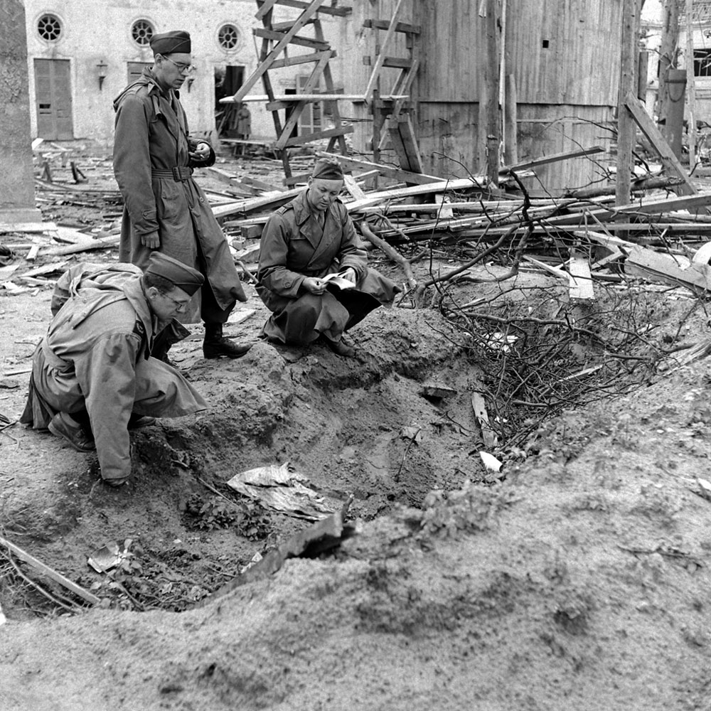 <b>Not published in LIFE.</b> LIFE correspondent Percy Knauth, left, sifts through debris in the shallow trench in the garden of the Reich Chancellery where, Knauth was told, the bodies of Hitler and Eva Braun were burned after their suicides.