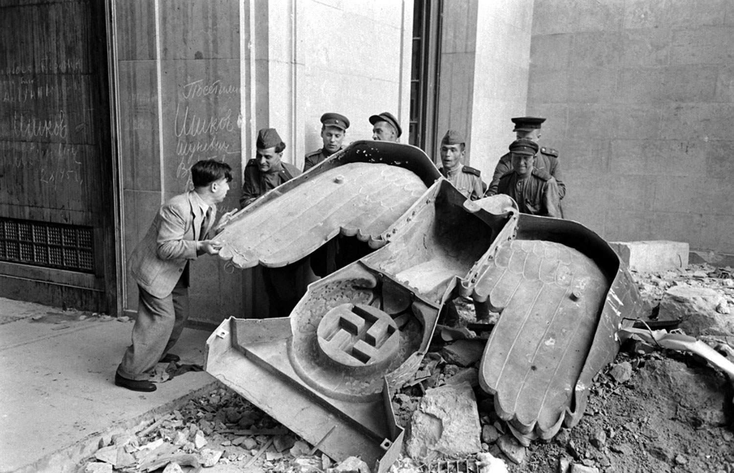 <b>Not published in LIFE.</b> Russian soldiers and a civilian struggle to move a large bronze Nazi Party eagle that once loomed over a doorway of the Reich Chancellery, Berlin, 1945.