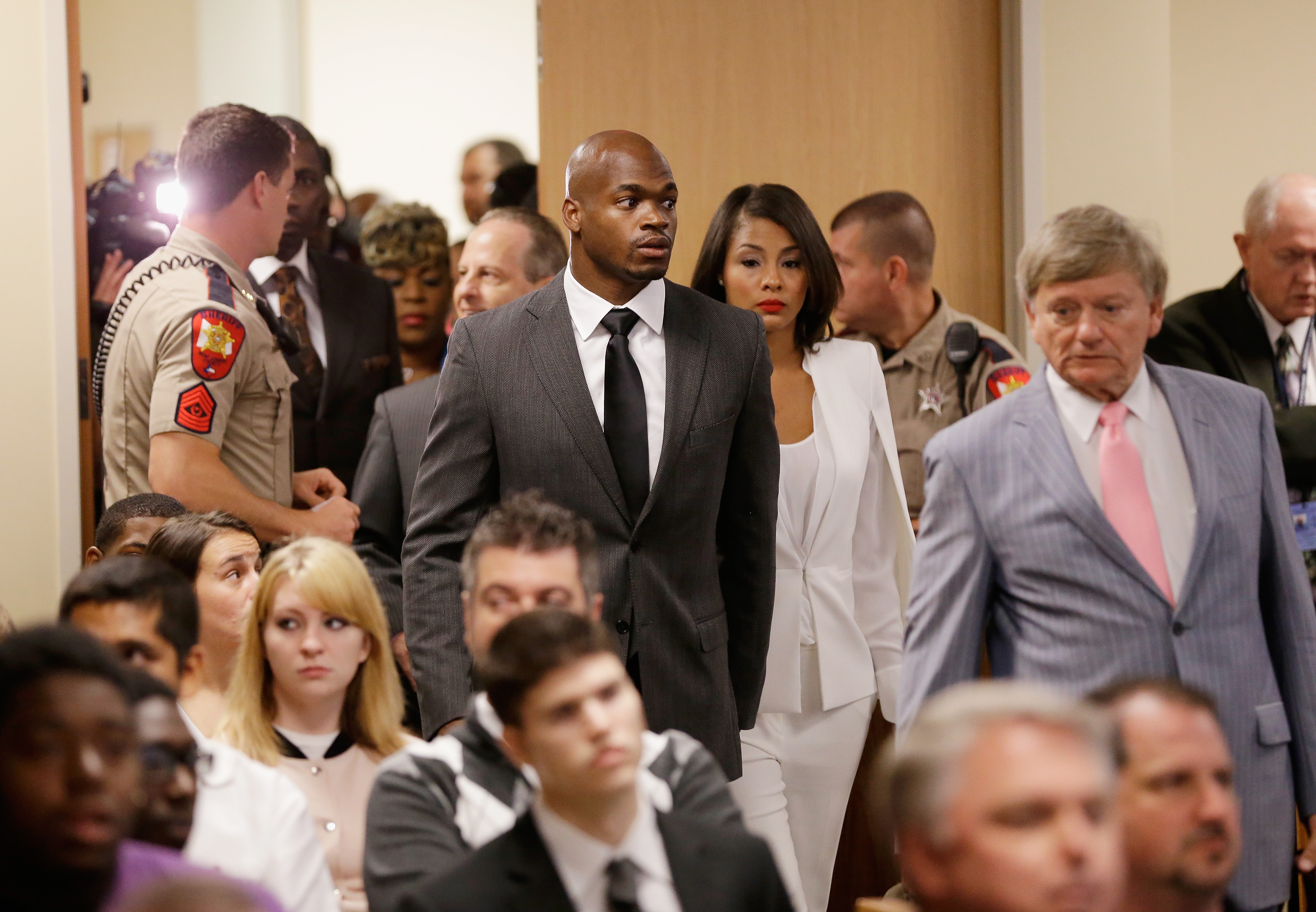From left: NFL player Adrian Peterson of the Minnesota Vikings  enters the courtroom with his wife Ashley Brown and his attorney Rusty Hardin on October 8, 2014 in Conroe, Texas.  Petersen is facing charges of reckless or negligent injury to a child.